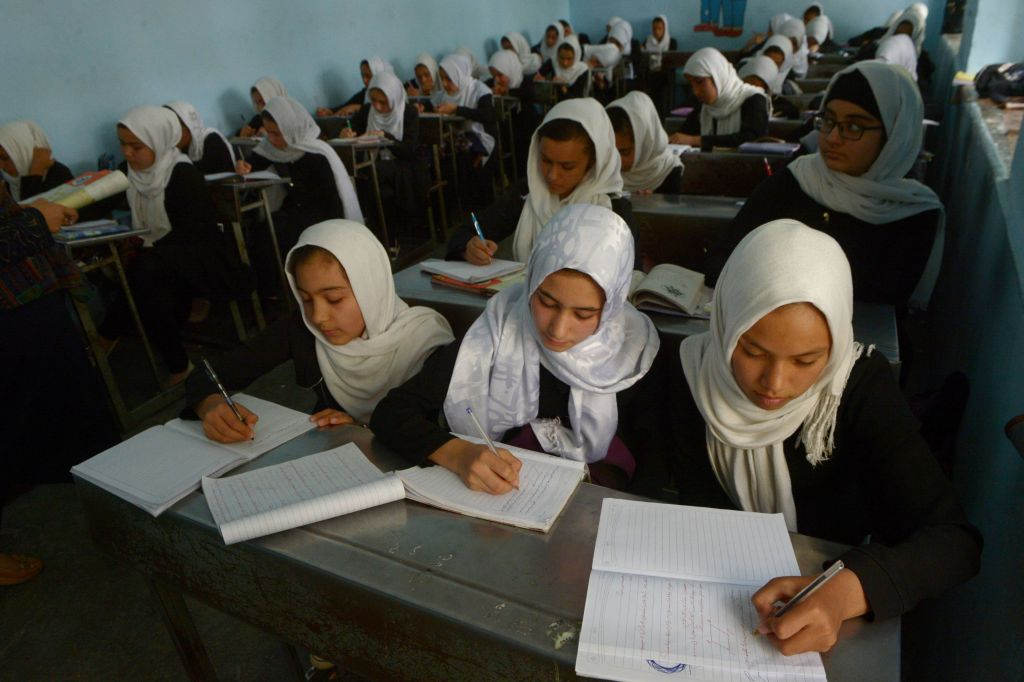 Afghan girls study during a lesson at a school in Herat province on October 17, 2017.