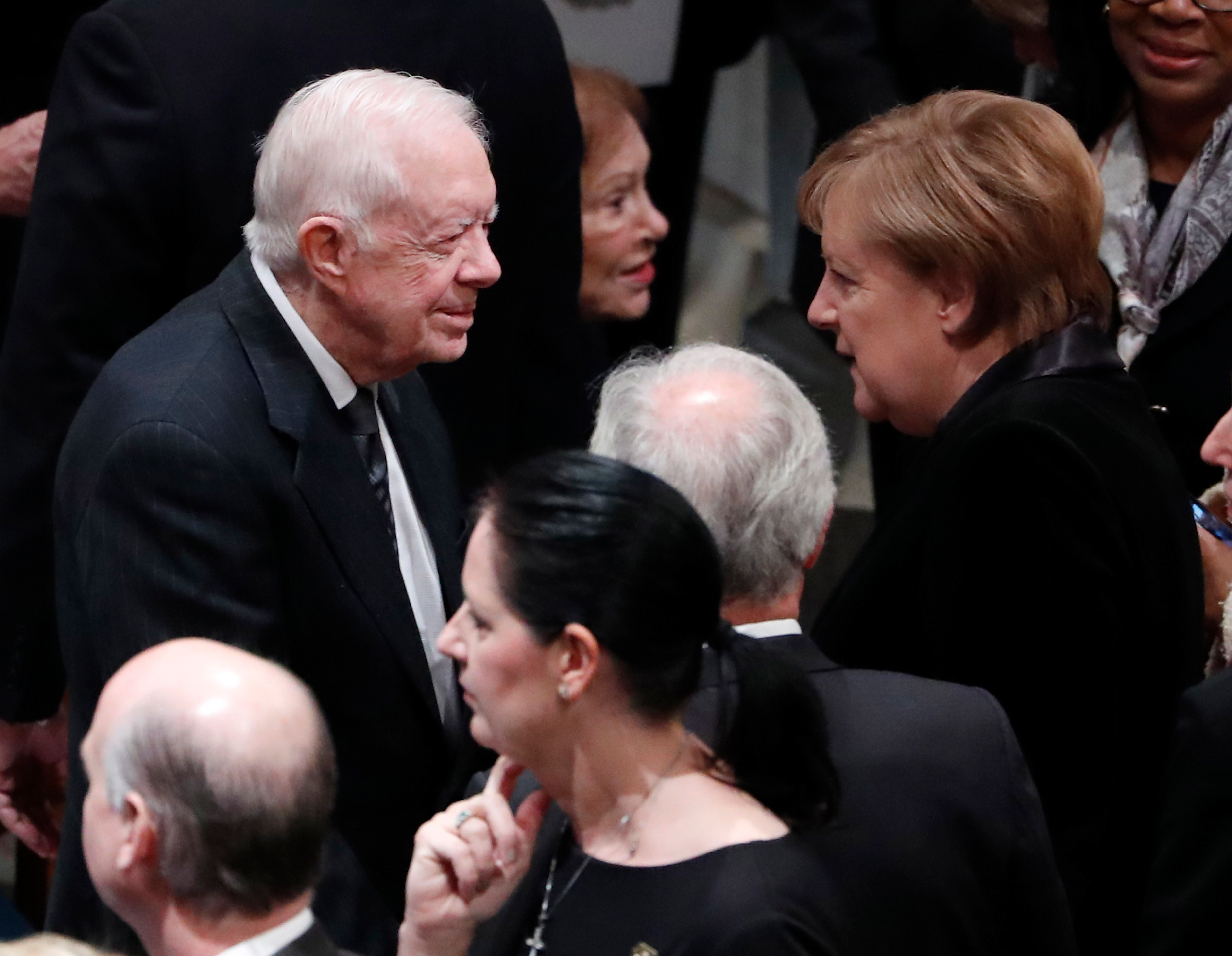 Former United States President Jimmy Carter talks with German Chancellor Angela Merkel as they arrive for the funeral services for former United States President George H. W. Bush at the National Cathedral, in Washington, DC on Dec. 5, 2018.