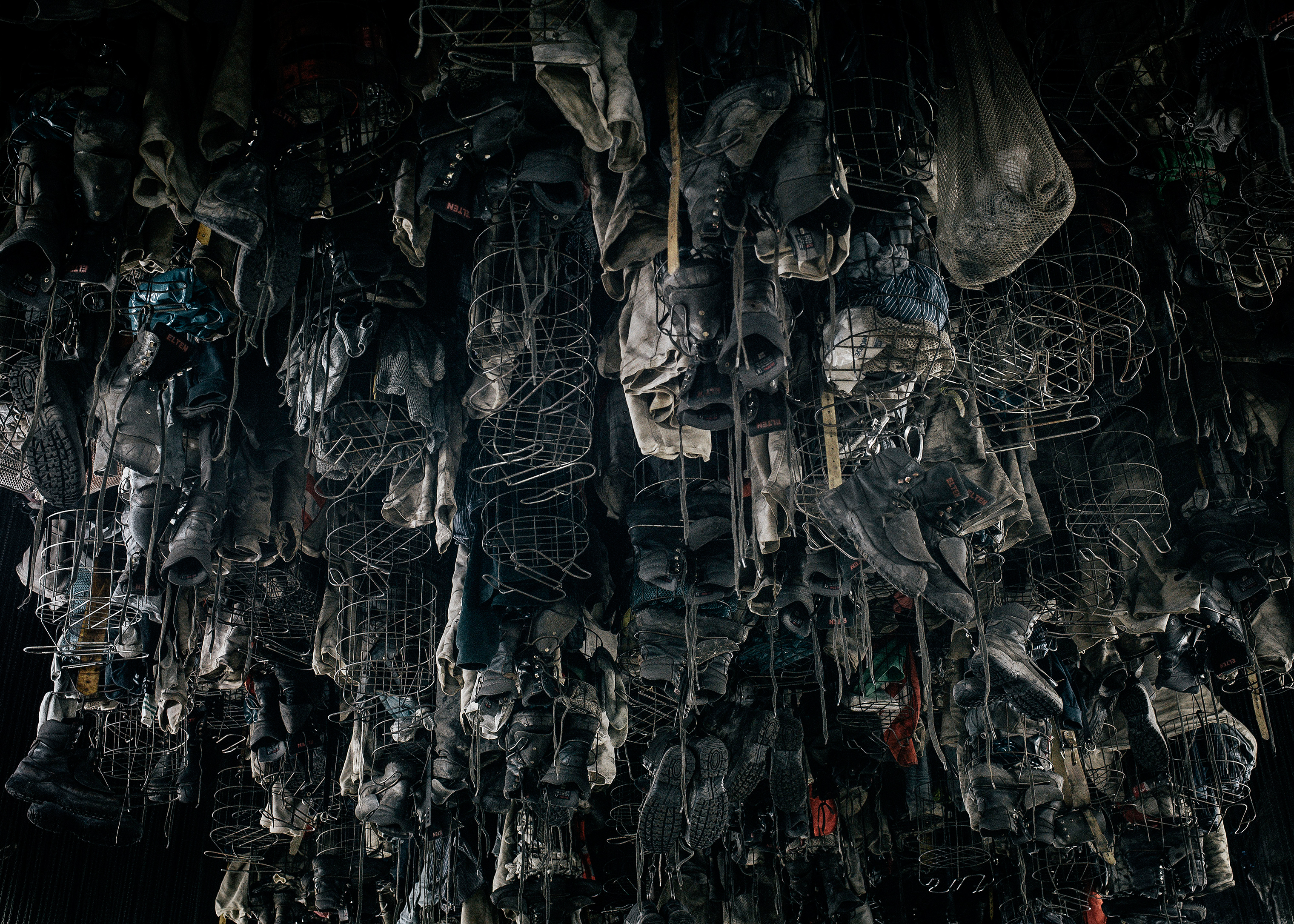 Miners' workwear dries and airs out while hanging from cages, pulled up to the ceiling by chains, in December 2017.