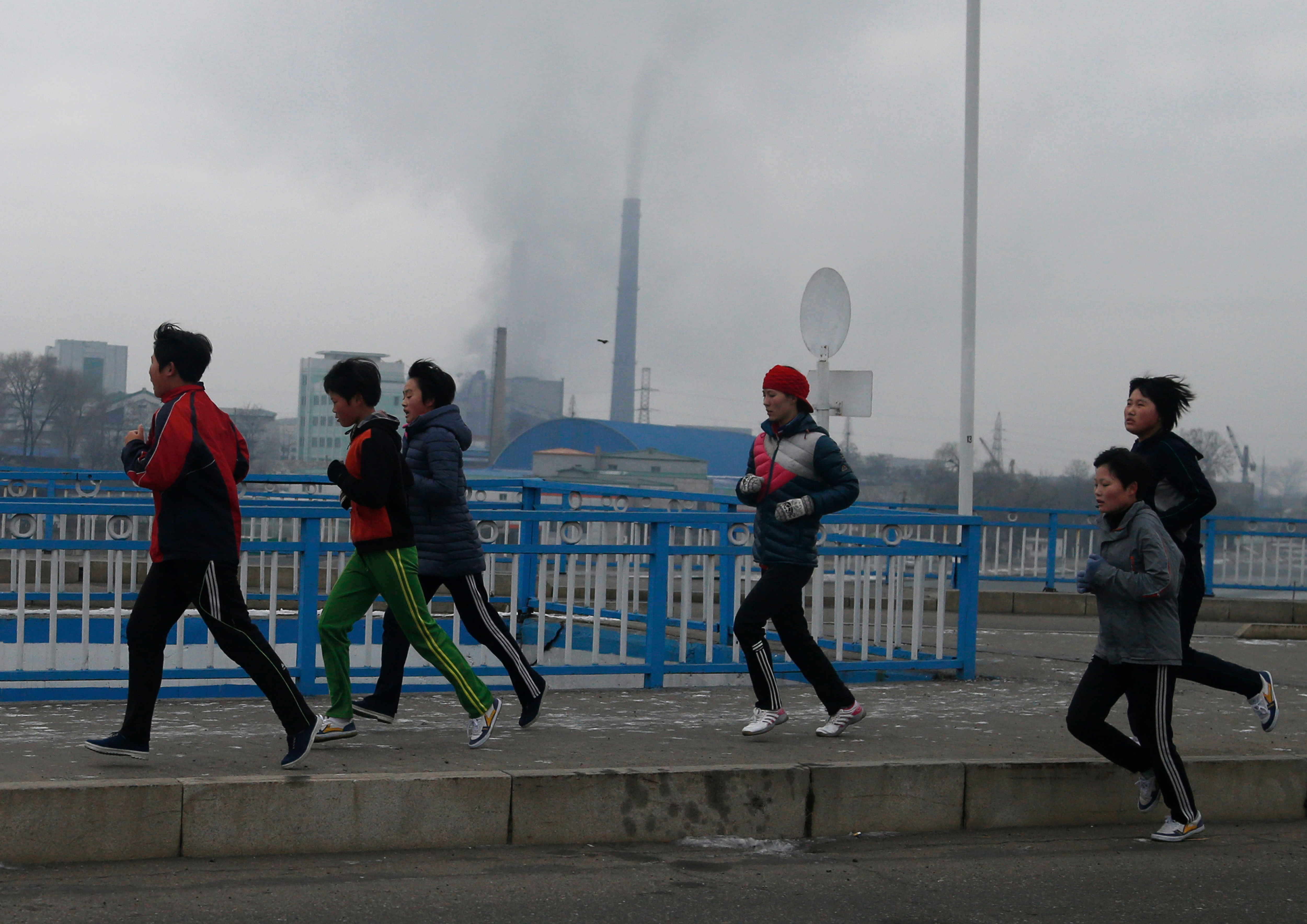 North Korean youths take their morning run as smoke billows from the chimneys of Pyongyang Power Plant in the background in Pyongyang, North Korea, on Dec. 15, 2018.