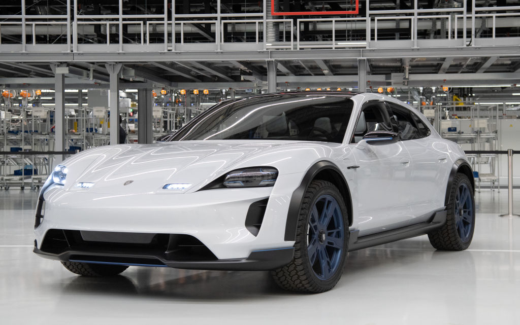 A study Porsche Mission E Cross Turismo stands in front of the assembly line for the Taycan E-drive.