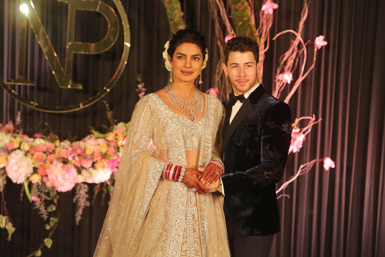 Newly-wed Bollywood actor Priyanka Chopra and American singer Nick Jonas pose for photos during their wedding reception, at Taj Palace on December 4, 2018 in New Delhi, India.