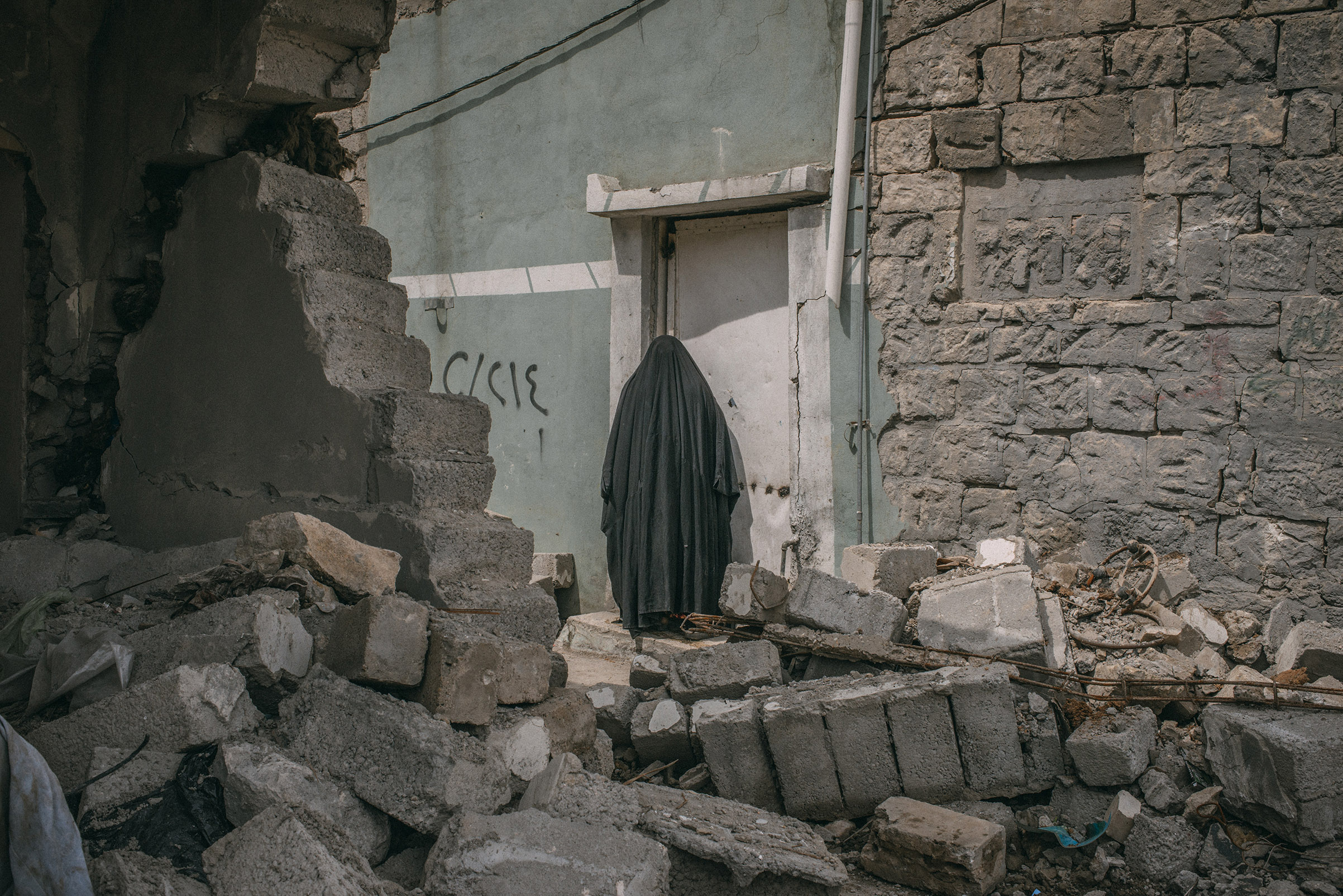 A woman stands among buildings damaged by airstrikes in southwest Mosul on April 3, 2017