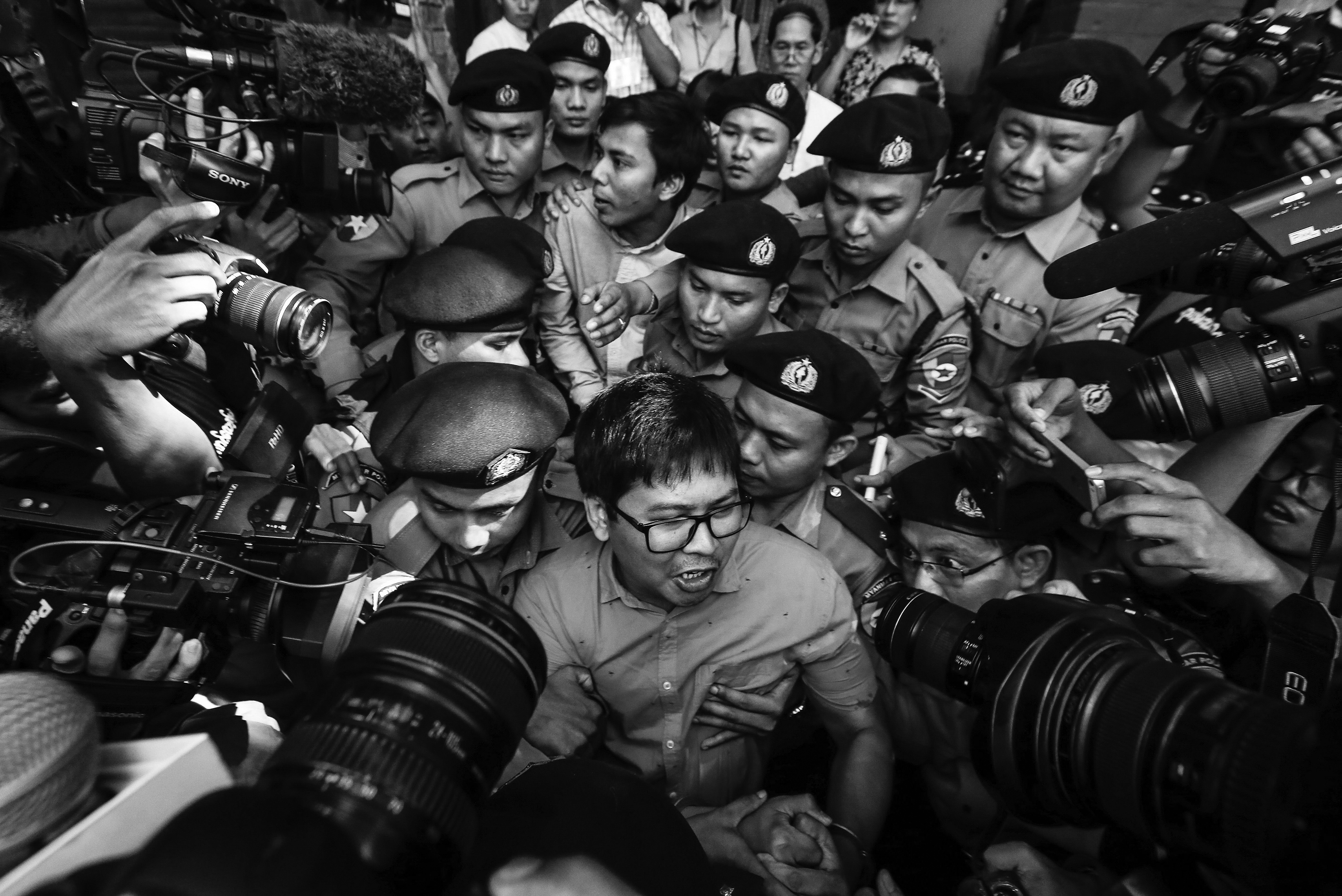 Reuters' journalists Wa Lone (C, front) and Kyaw Soe Oo (C, back) are escorted by police as they leave the court after their first trial in Yangon, Myanmar, 10 January 2018. Reuters journalists Wa Lone and Kyaw Soe Oo were arrested on the outskirts of Yangon city on 12 December 2017 by Myanmar police for allegedly possessing classified police documents. In September the journalists were convicted to seven years in prison.