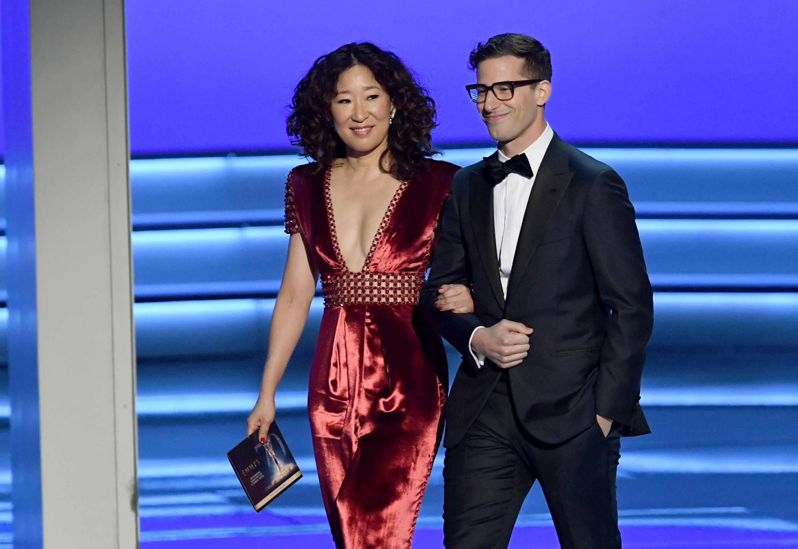 Sandra Oh (L) and Andy Samberg walk onstage during the 70th Emmy Awards at Microsoft Theater on September 17, 2018 in Los Angeles, California.