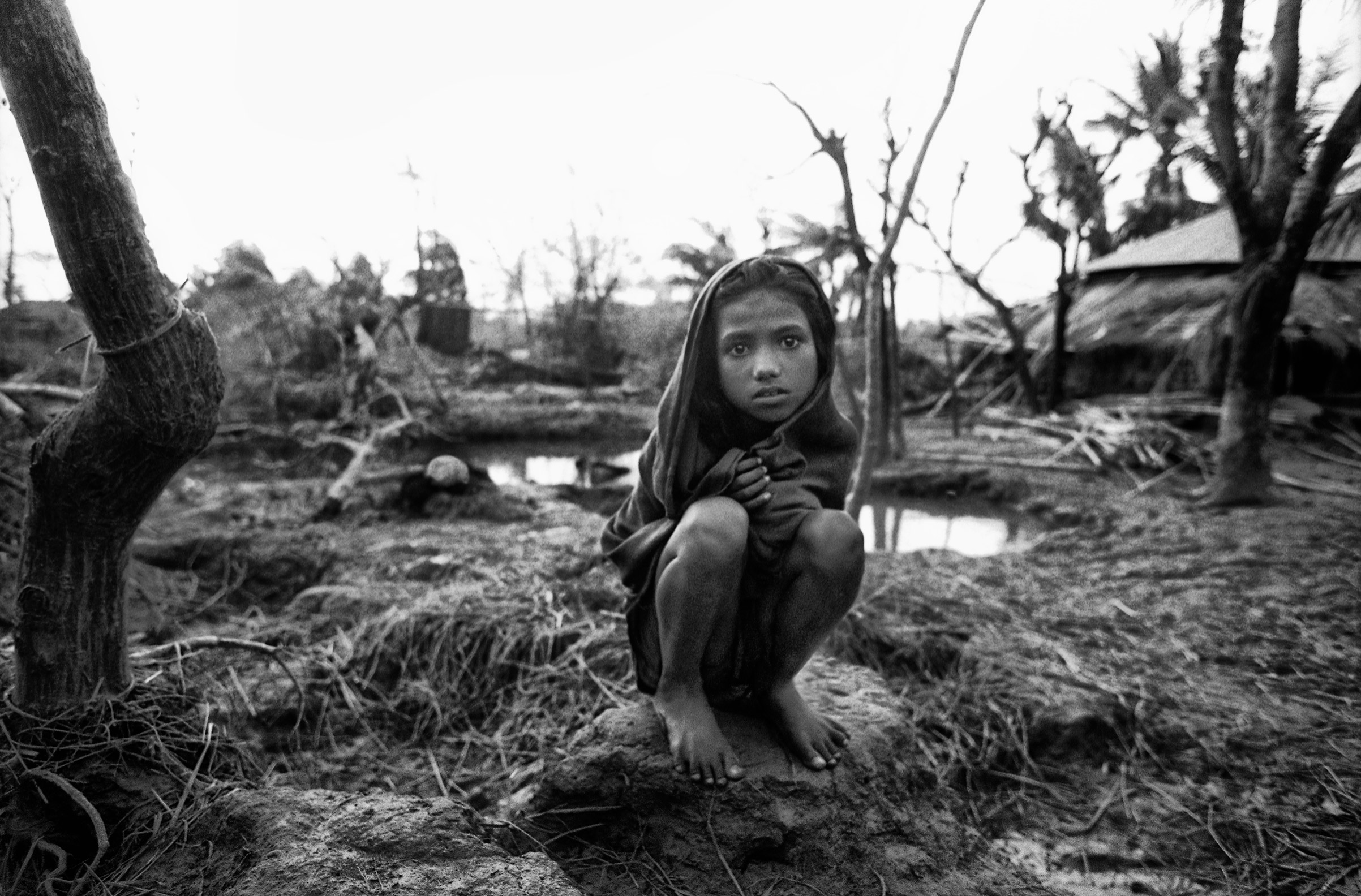 A girl crouches near the remains of her home in the aftermath of a deadly storm in Anwara, Chittagong, Bangladesh, 1991.