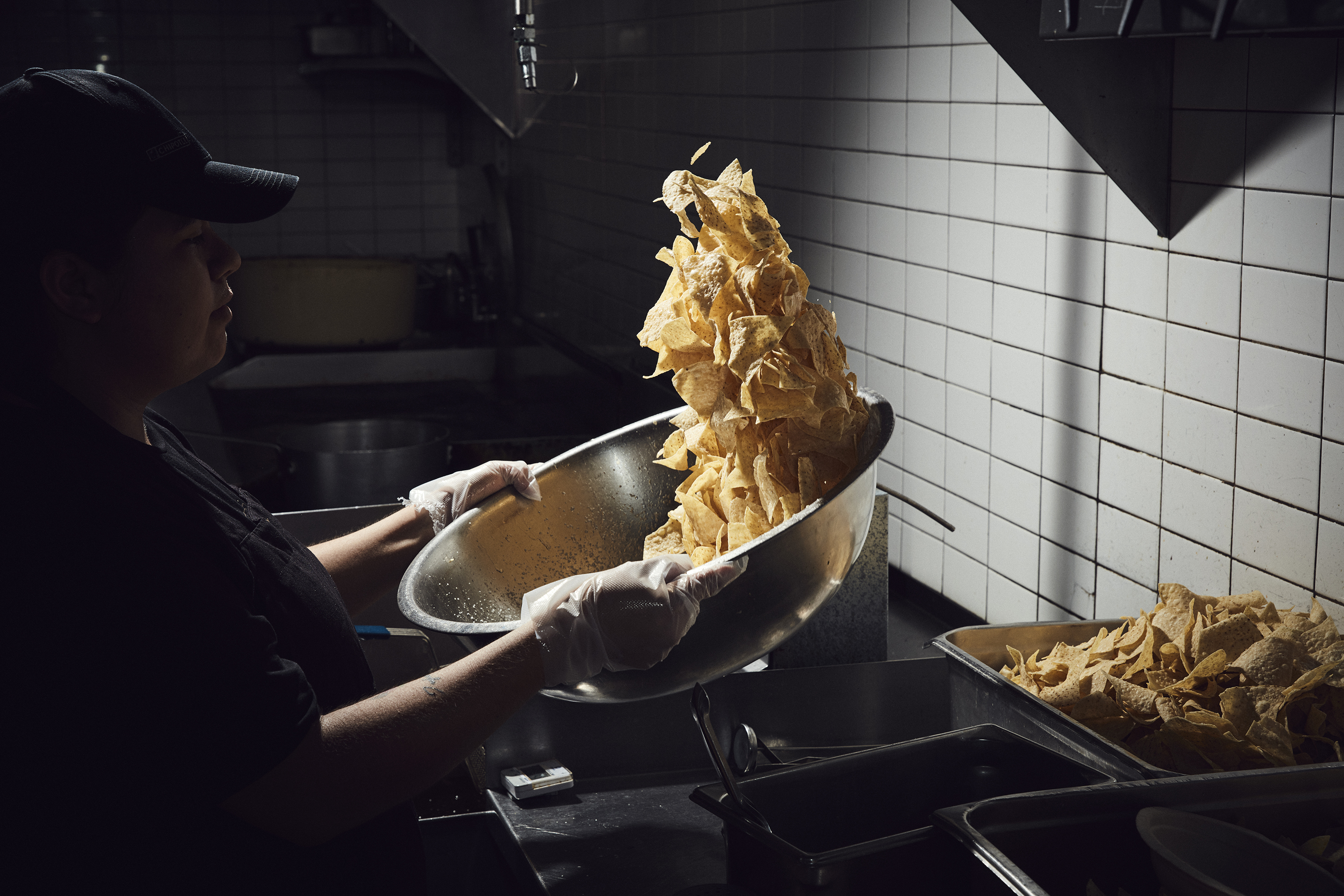 A Chipotle employee seasons chips at a location in Newport Beach, Calif. The company, founded in 1993, now has roughly 70,000 employees and 2,450 locations.