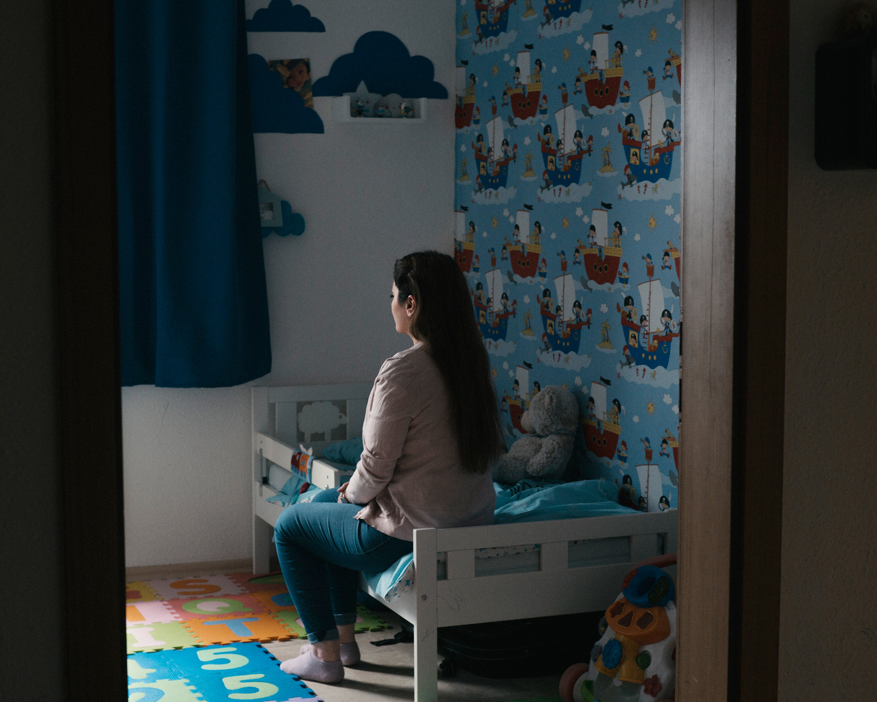 Aya sits in the bedroom where her 2-year-old son Joud once slept. Her husband took Joud back to Syria after she asked for a divorce.