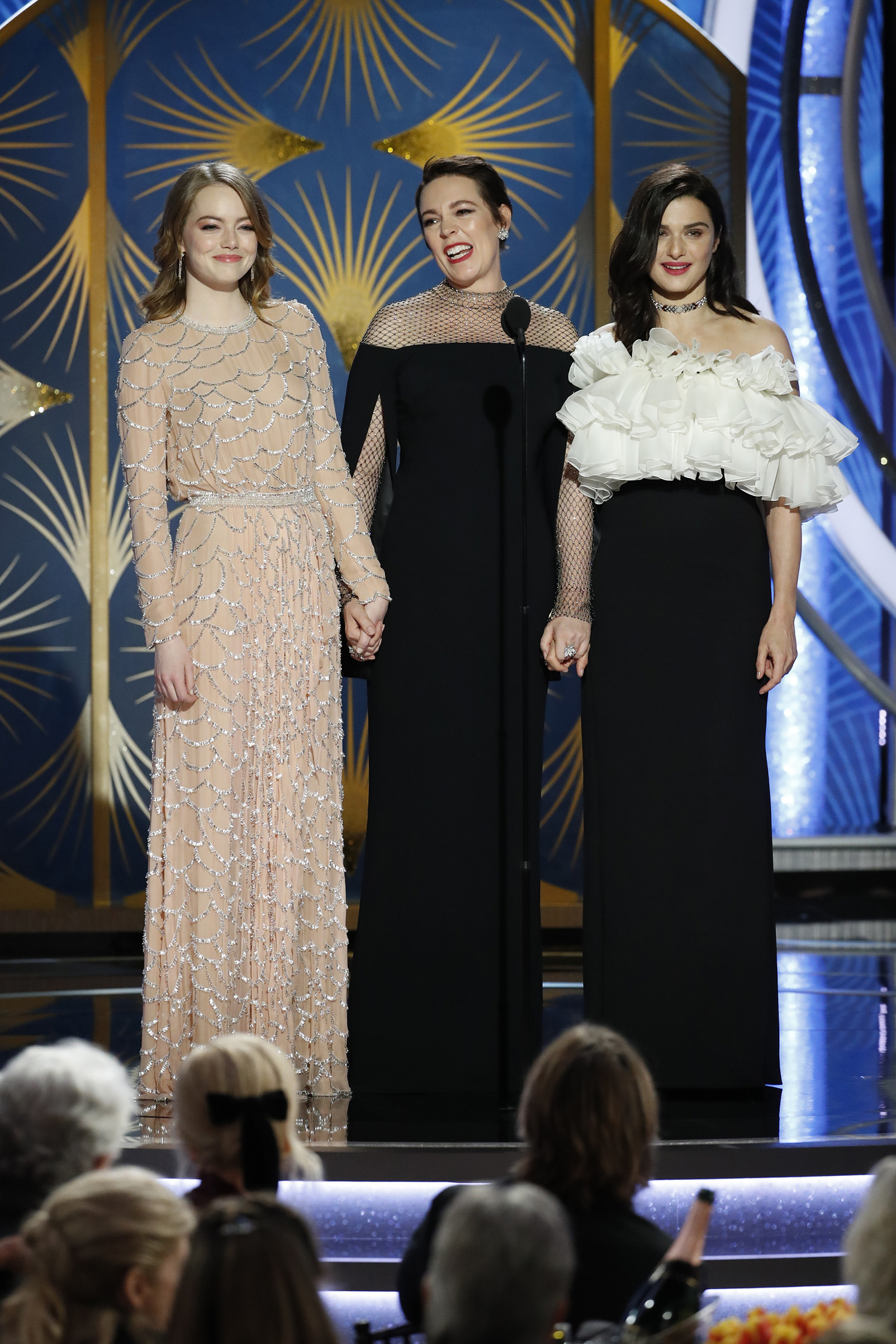 Emma Stone, Olivia Colman, and Rachel Weisz speak onstage during the 76th Annual Golden Globe Awards.