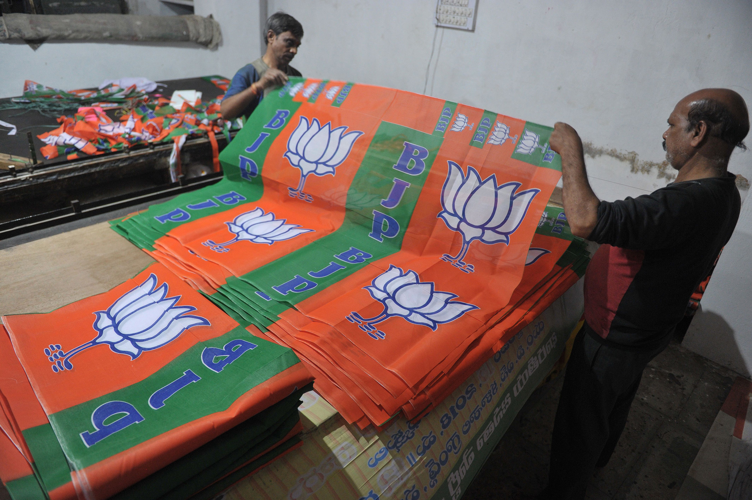 Indian labourers work at a workshop making Bharatiya Janata Party (BJP) election campaign banners for the Telangana state legislative assembly elections in Hyderabad.