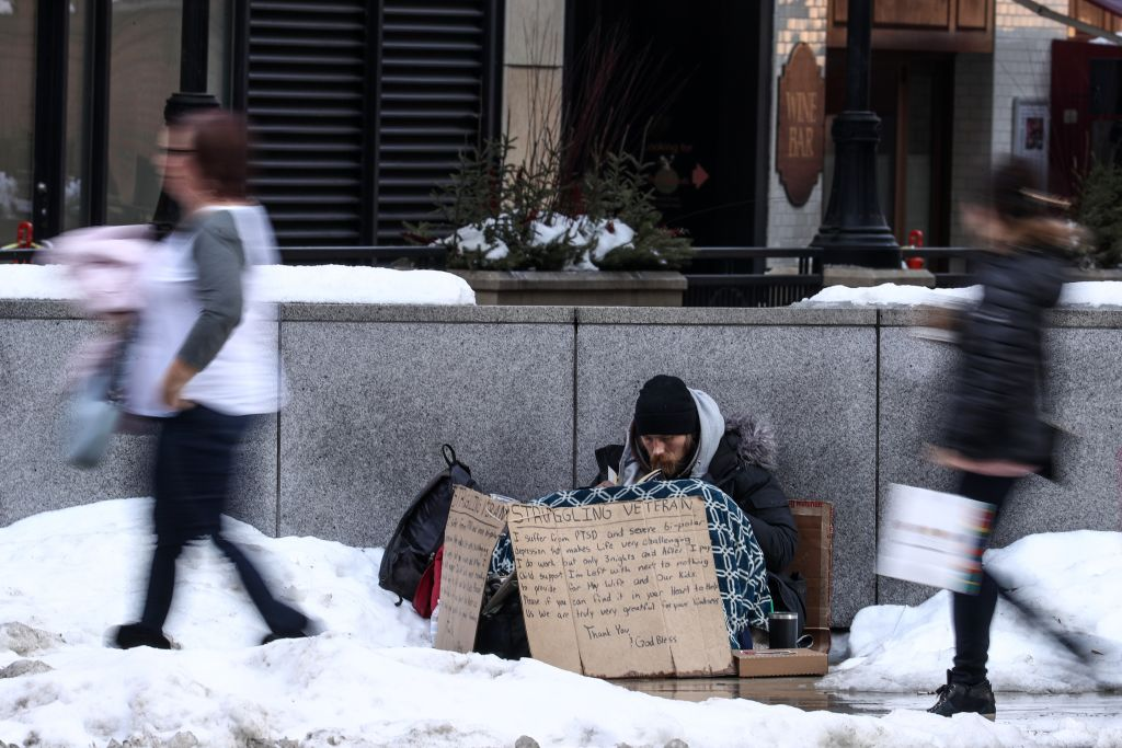 A homeless person tries to stay warm on a street while panhandling during freezing temperatures in Chicago, United States on February 16, 2018.