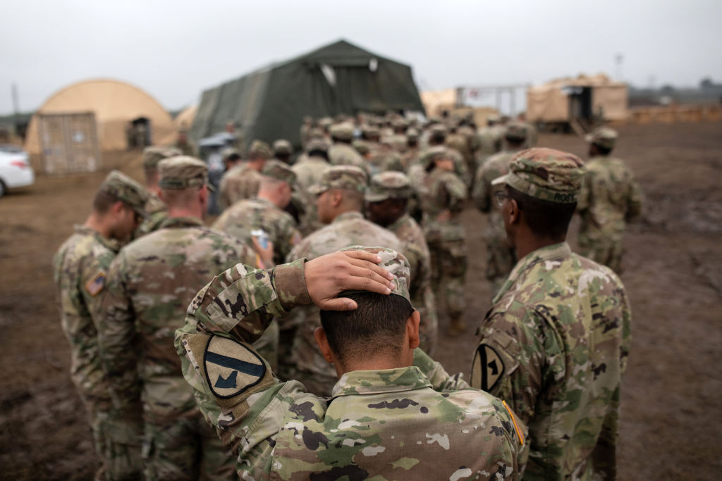 U.S. Army troops deployed to the U.S.-Mexico border line up to receive a Thanksgiving meal at a base near the Donna-Rio Bravo International Bridge on Nov. 22, 2018 in Donna, Texas. The U.S. Department of Defense released a report on Jan. 18, 2019 warning about the effects of climate change to armed forces and bases in the future.