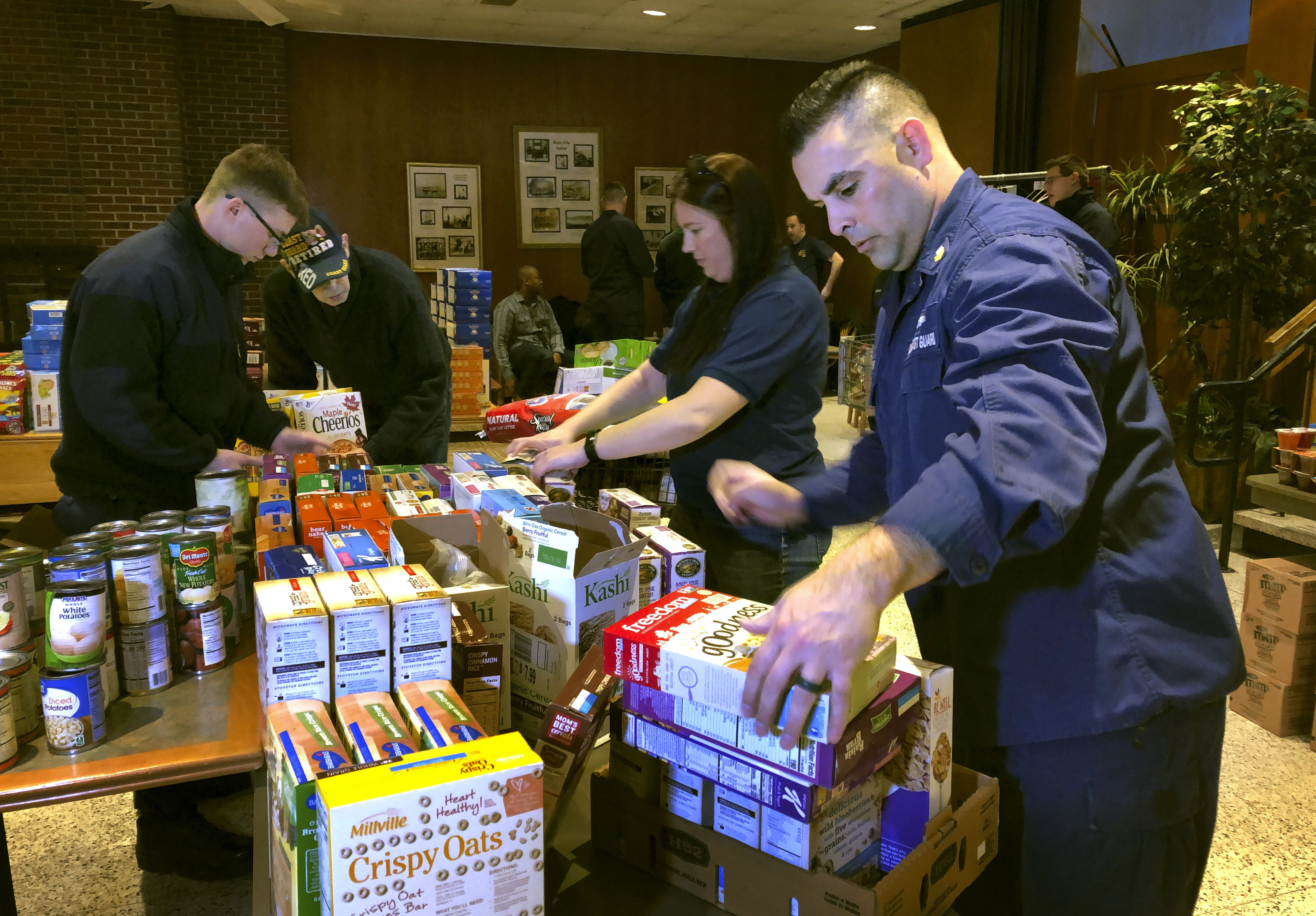U.S. Coast Guard Culinary Specialist Jerry Wright, right, and Petty Officer 2nd Class Lauren Laughlin, second from right, stack boxes of donated cereal at a pop-up food pantry created at the Coast Guard Academy in New London, Conn., on Jan. 17, 2019.