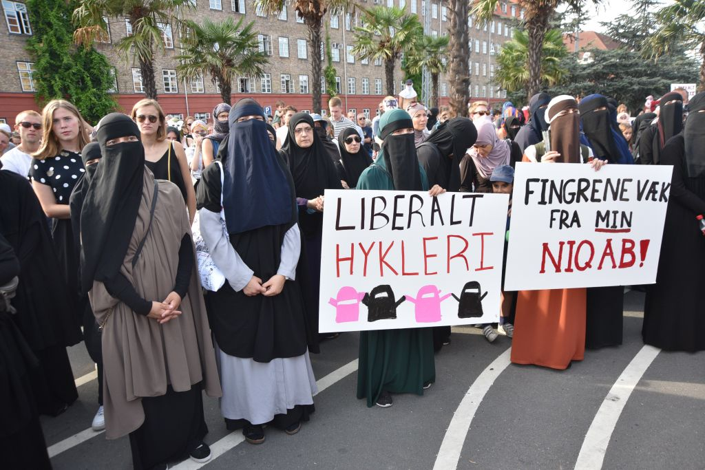 Demonstrators with face veils, hold placards and banners as they gather to protest ban on the wearing of face veils at the Black Square in Copenhagen, Denmark on August 01, 2018.