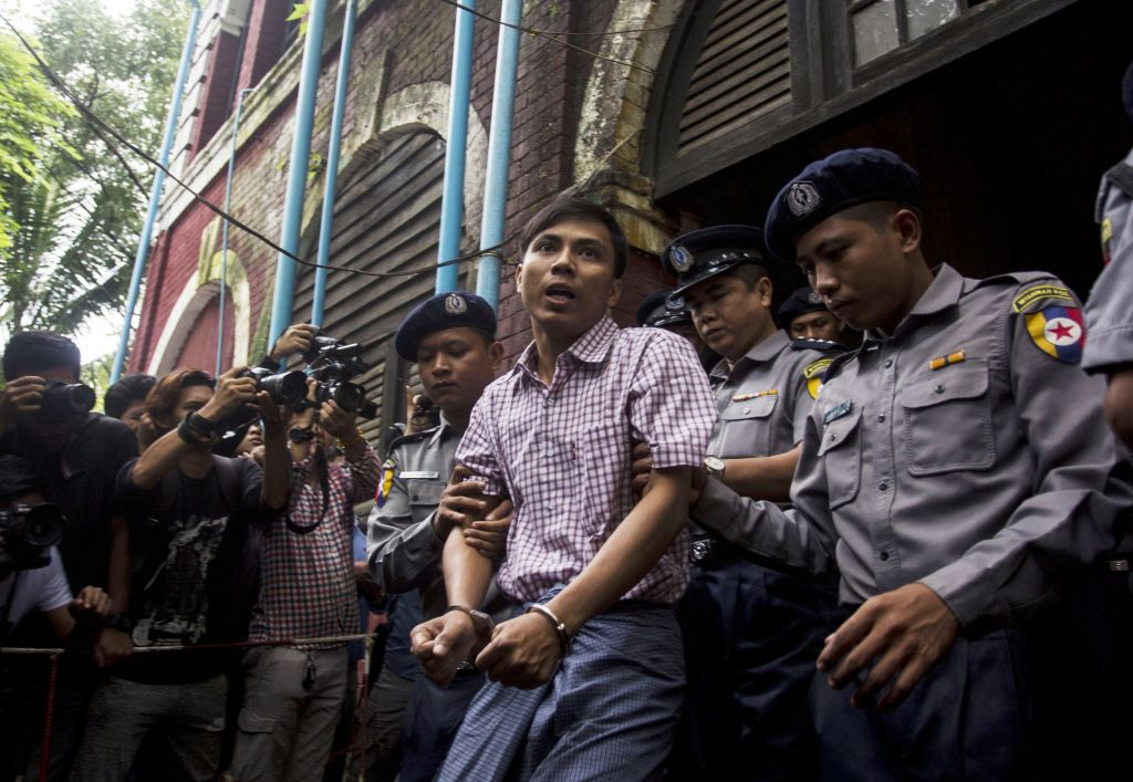 Detained Reuters journalist Kyaw Soe Oo  is escorted by police out of a court in Yangon, Myanmar on Aug. 27, 2018.
