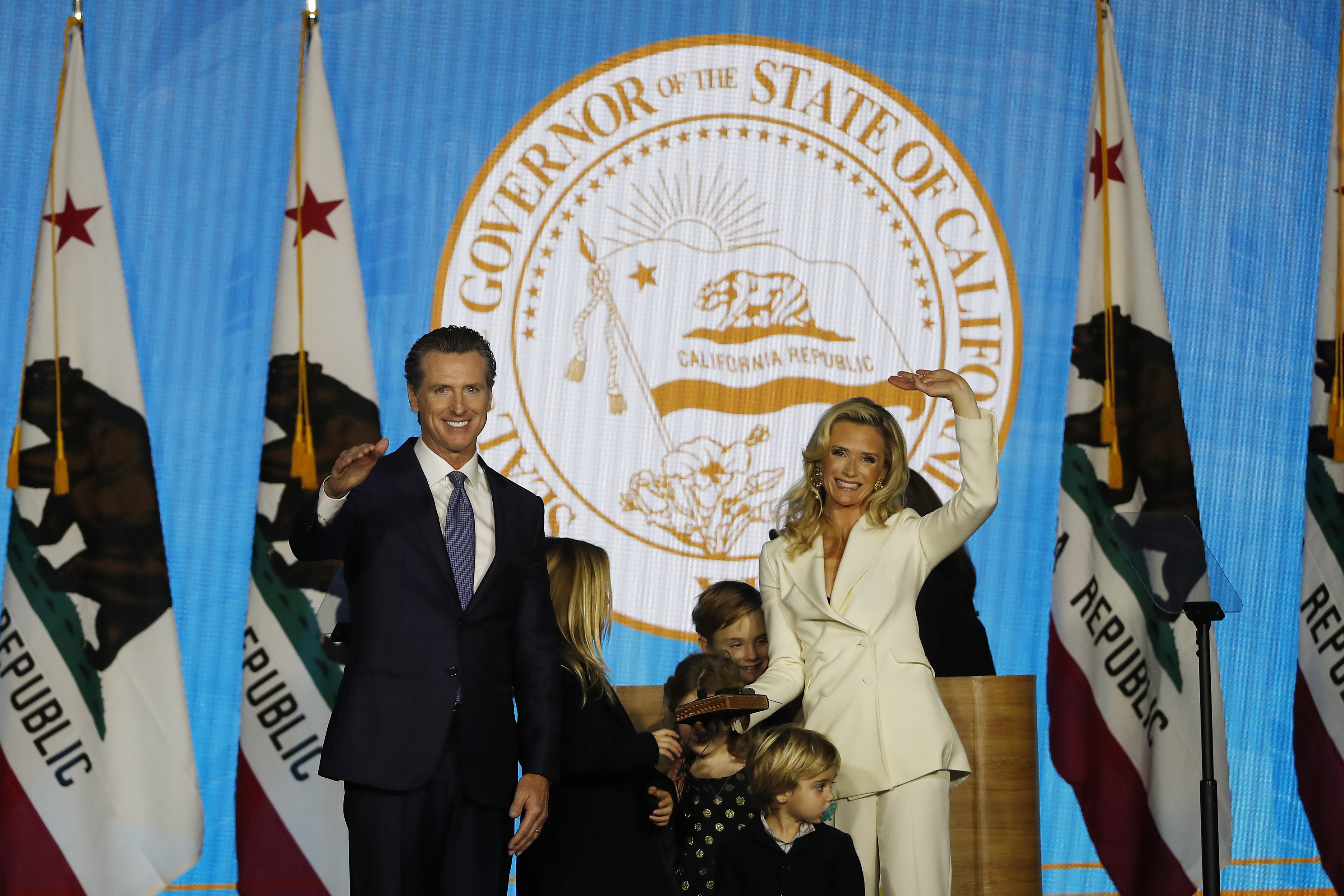 Governor Gavin Newsom and wife Jennifer Siebel Newsom gesture to the crowd after taking his oath of office on Jan. 7, 2019 in Sacramento, Calif.