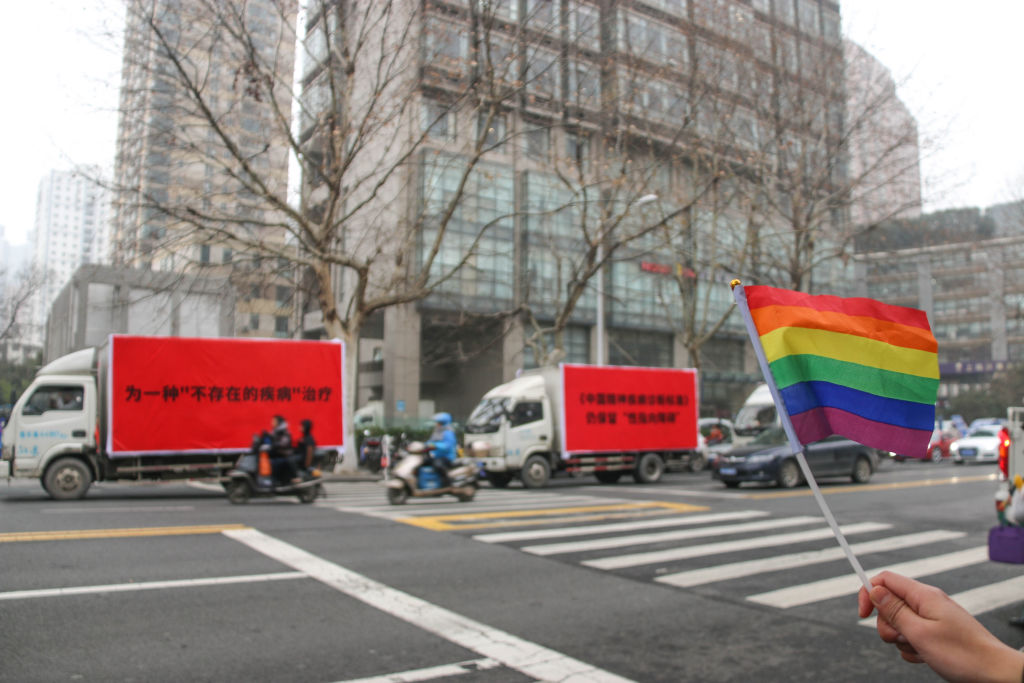 An activist waves a rainbow flag near trucks with slogans opposing  gay conversion therapy  in Nanjing, China on Jan. 14, 2019.