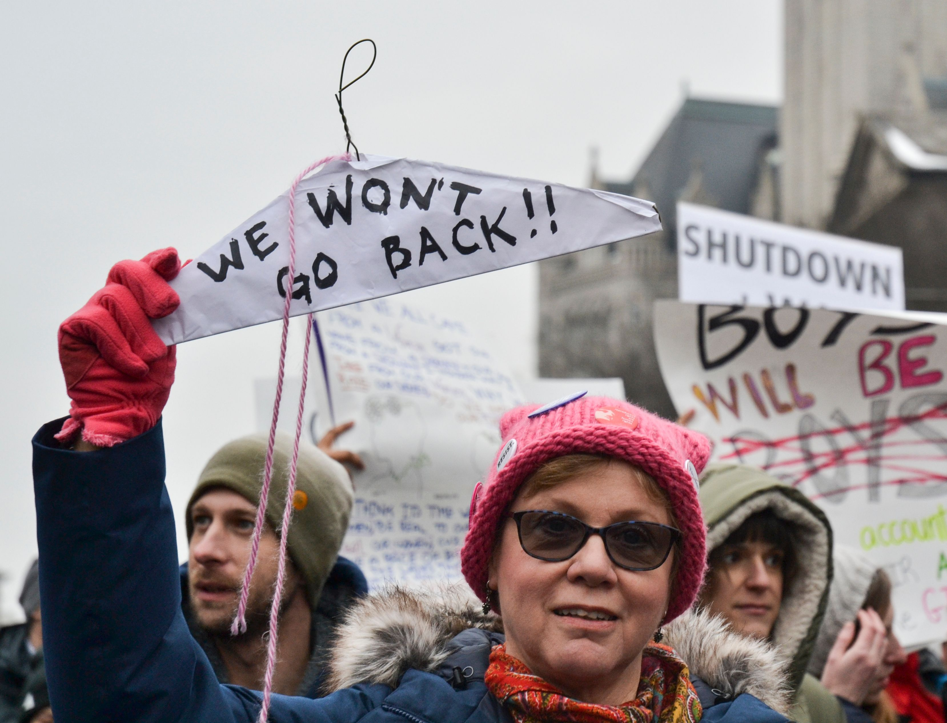 Protesters display their signs in front of the Trump Tower during the Women's March in Washington, DC January 19, 2019.