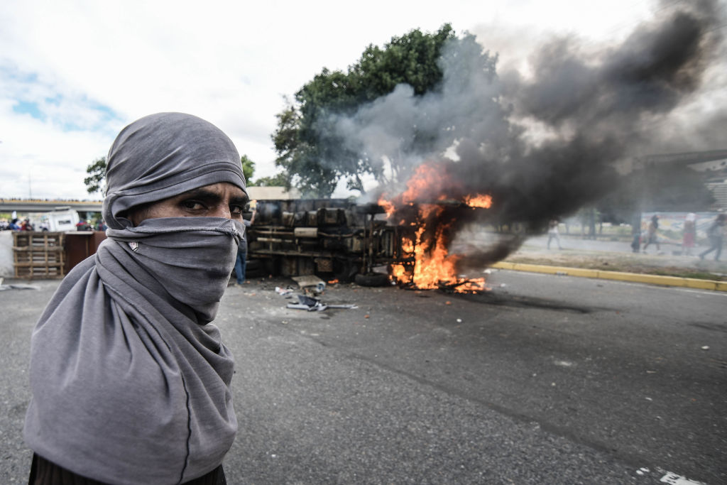A protester stands near burning barricades during a demonstration against Nicolas Maduro in Caracas on Jan. 23, 2019.