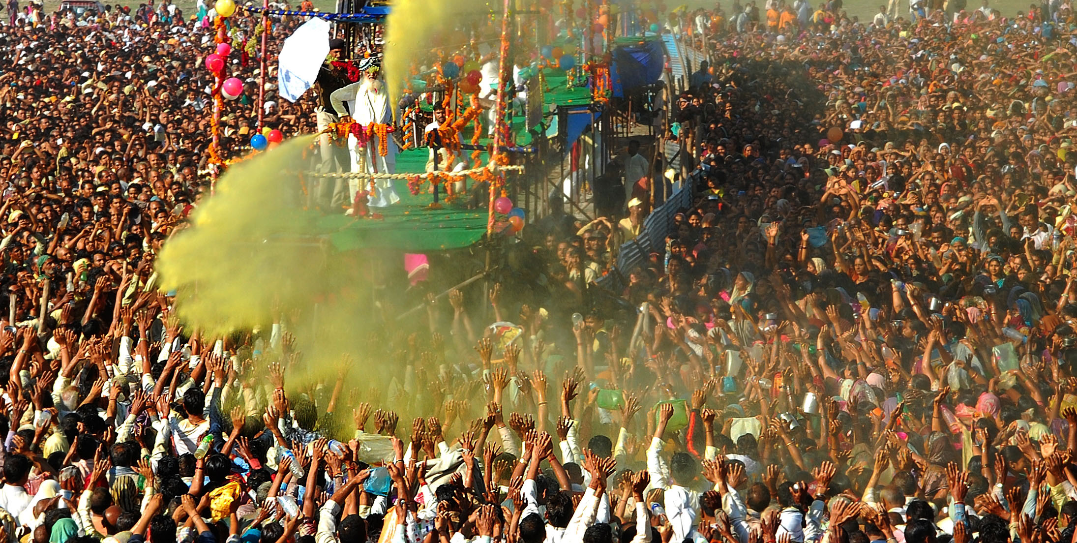 Sant Shri Asaram Bapu sprinkling colored water on his thousands of followers as part of Holi celebrations in Kumbh Mela on March 9, 2013 in Allahabad, India.