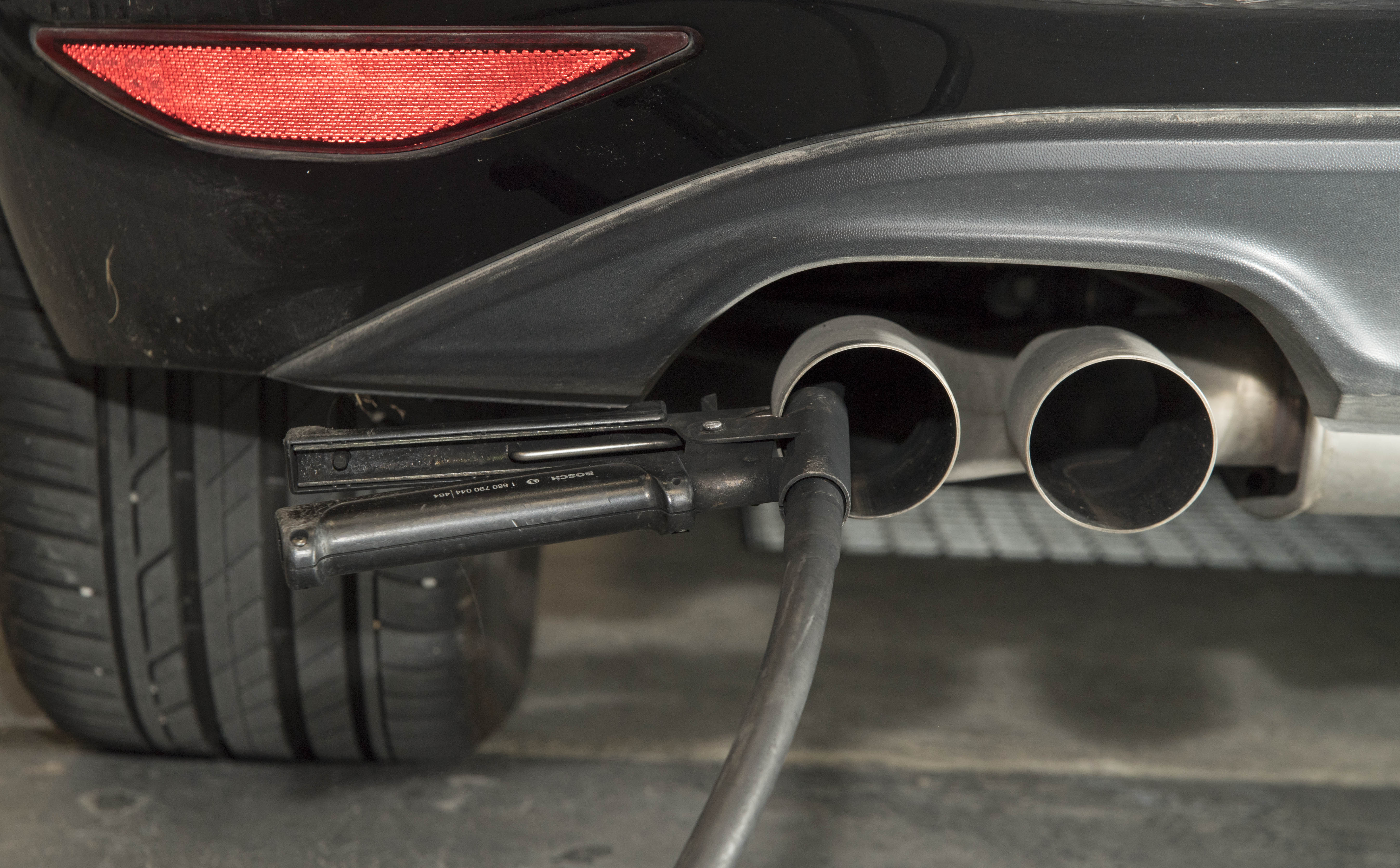 A hose for an emission test is fixed in the exhaust pipe of a car at the Technical Inspection Agency in Ludwigsburg, southwestern Germany, on Aug. 7, 2017.