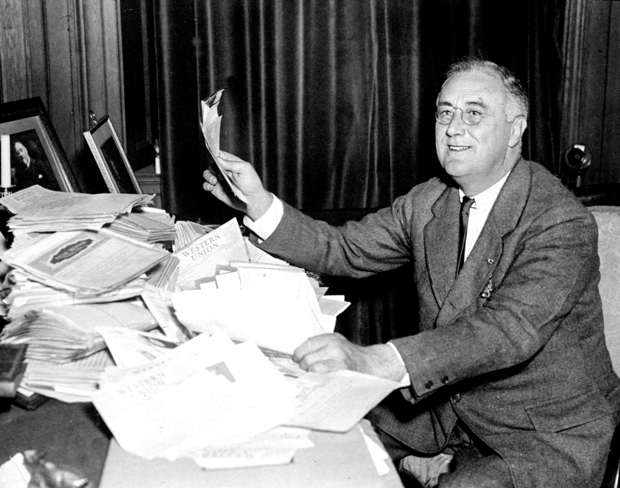 President Franklin D. Roosevelt reads congratulatory telegrams on Nov. 4, 1936, after re-election victory over Alfred Landon.