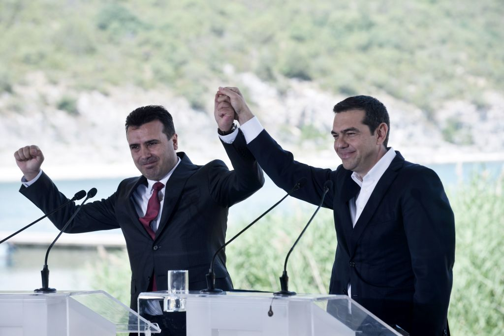 Greek Prime Minister Alexis Tsipras (R) and Macedonian Prime Minister Zoran Zaev raise their hands during a signing ceremony between officials from Greece and Macedonia at Prespes Lake on June 17, 2018.
