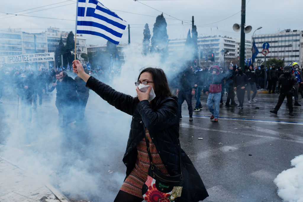 A woman holds the Greek flag during riots in a rally over Macedonia name row in Syntagma square, central Athens on January 20, 2019. Violent clashes broke out during a rally held in the Greek capital to protest against a name deal with the neighboring Republic of Macedonia ahead of a parliamentary vote to ratify the the so-called Prespes agreement.
