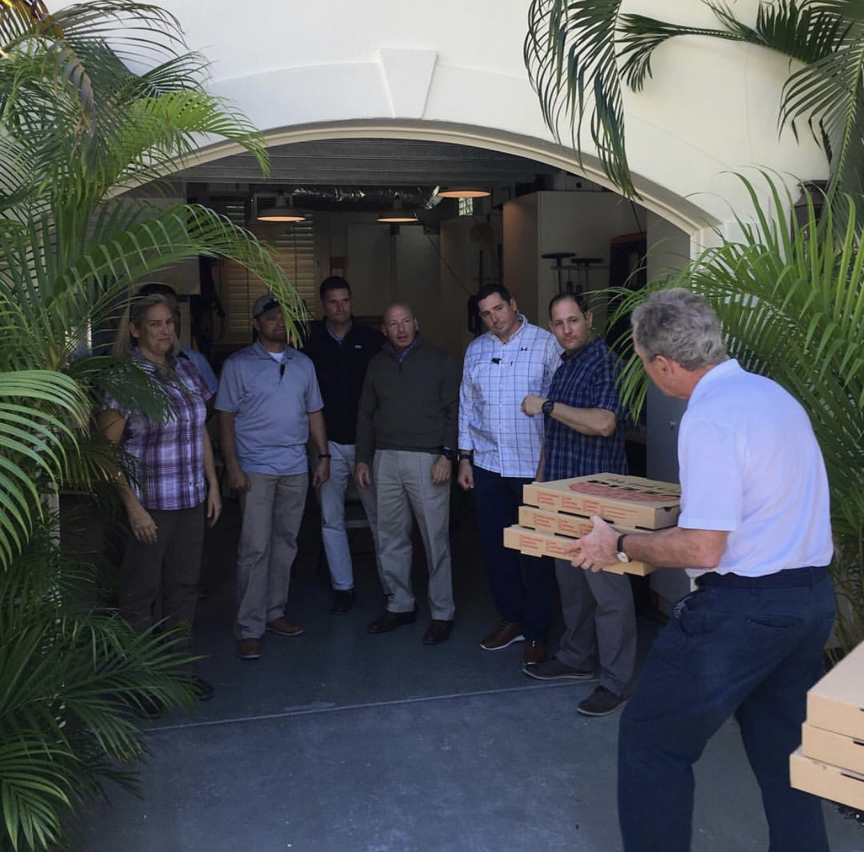 Former president George W. Bush hands pizza to his secret service personnel.