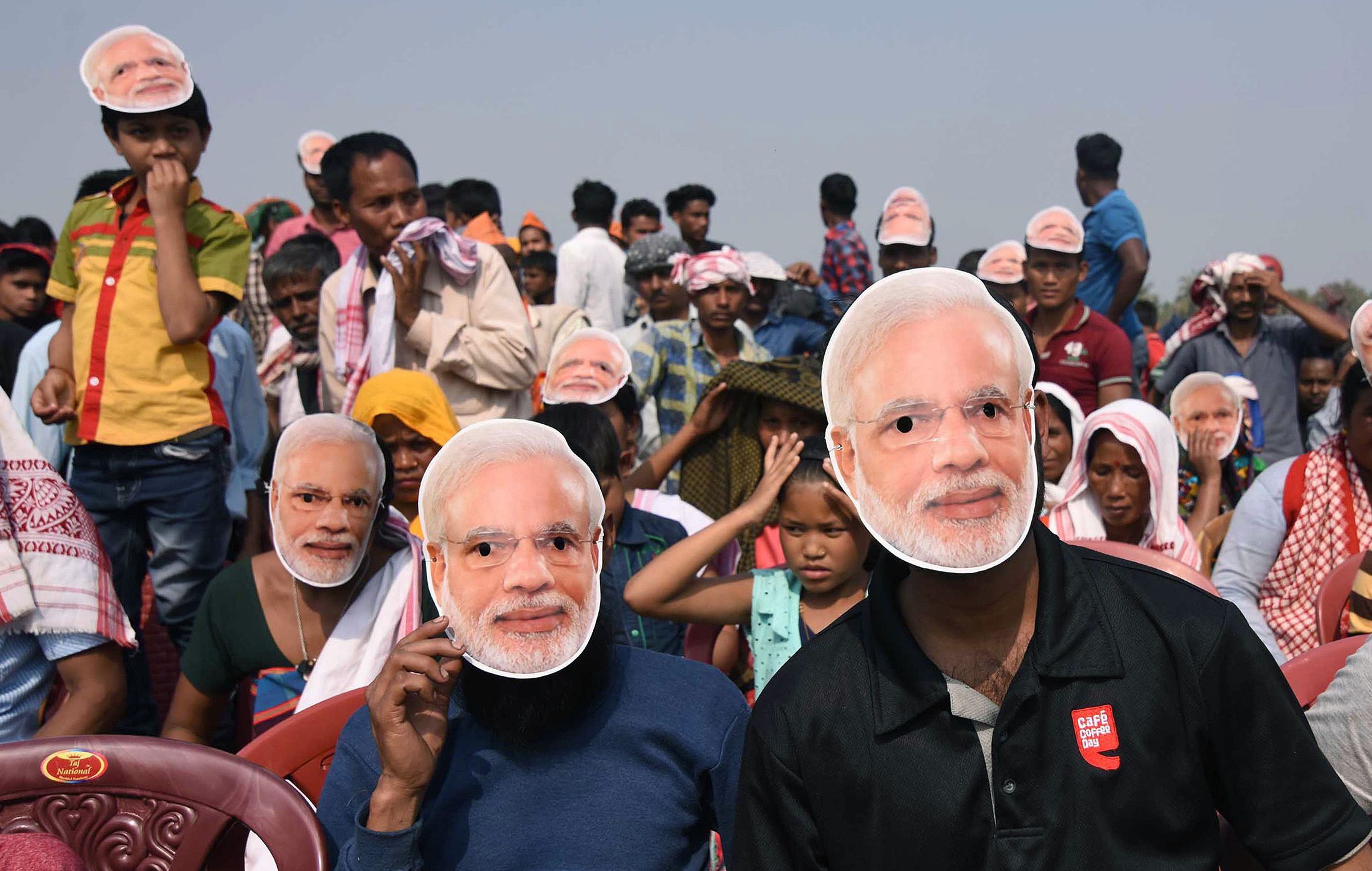 Supporters of the Bharatiya Janata Party (BJP) wearing masks of Indian Prime Minister Narendra Modi listen to Modi during an election rally at Phulbari in west Garo hills of Meghalaya on Feb 22, 2018.
