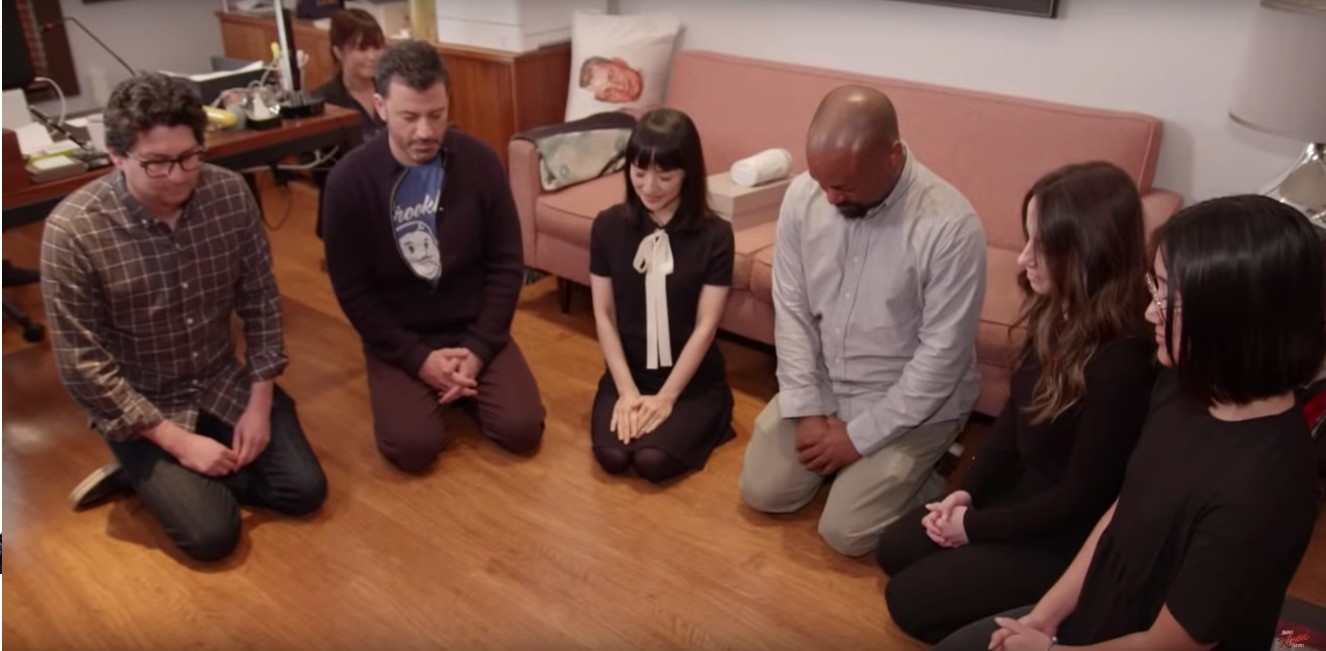 In this screenshot from video, Jimmy Kimmel and Marie Kondo are seen on Jimmy Kimmel Live on Jan. 29, 2019 in a prayer circle before they  tidy up .