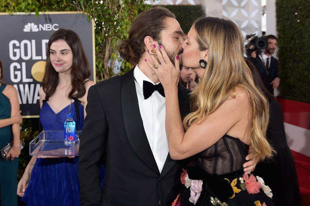 Kelleth Cuthbert walks by as Heidi Klum kisses her fiancé Tom Kaulitz at the 76th Annual Golden Globe Awards on Jan. 6, 2019 at the Beverly Hilton in Los Angeles, California.