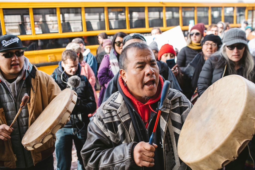 Sleepy Eye LaFromboise beat a drum in front of Nathaniel Hall, a diocese member, at a protest outside the Covington Catholic Diocese on January 22, 2019.