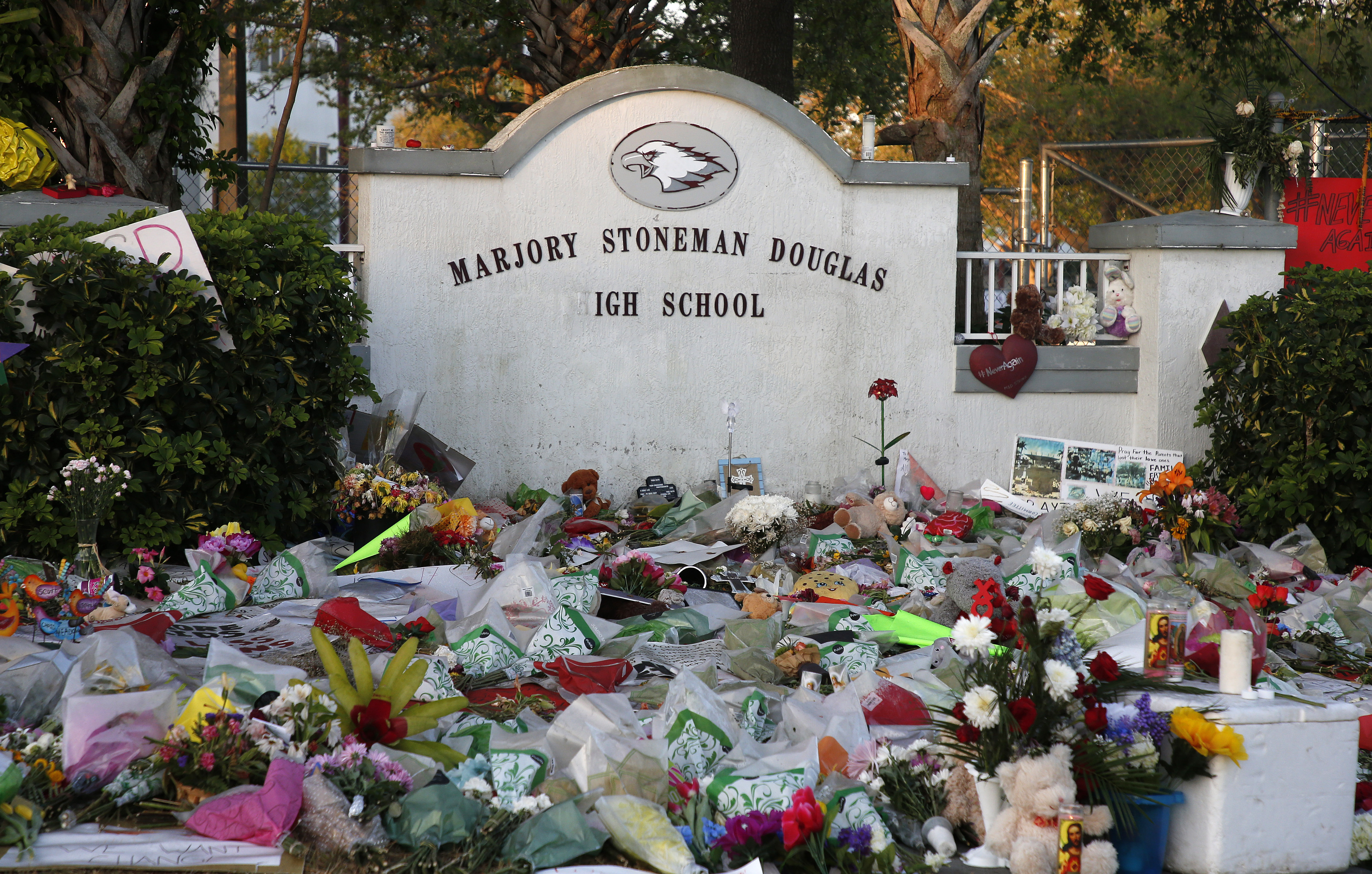 Flowers, candles and mementos sit outside one of the makeshift memorials at Marjory Stoneman Douglas High School in Parkland, Florida on February 27, 2018.