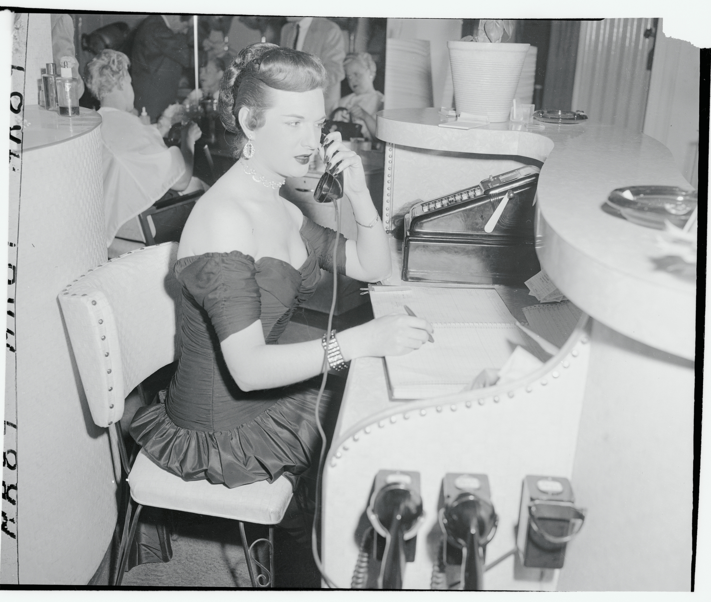 Charlotte McLeod is shown at her desk on her first day at a new job as a makeup artist and receptionist, on Feb. 10, 1955, in New York City. The original caption provided with the photo specified that she was an  Ex GI.