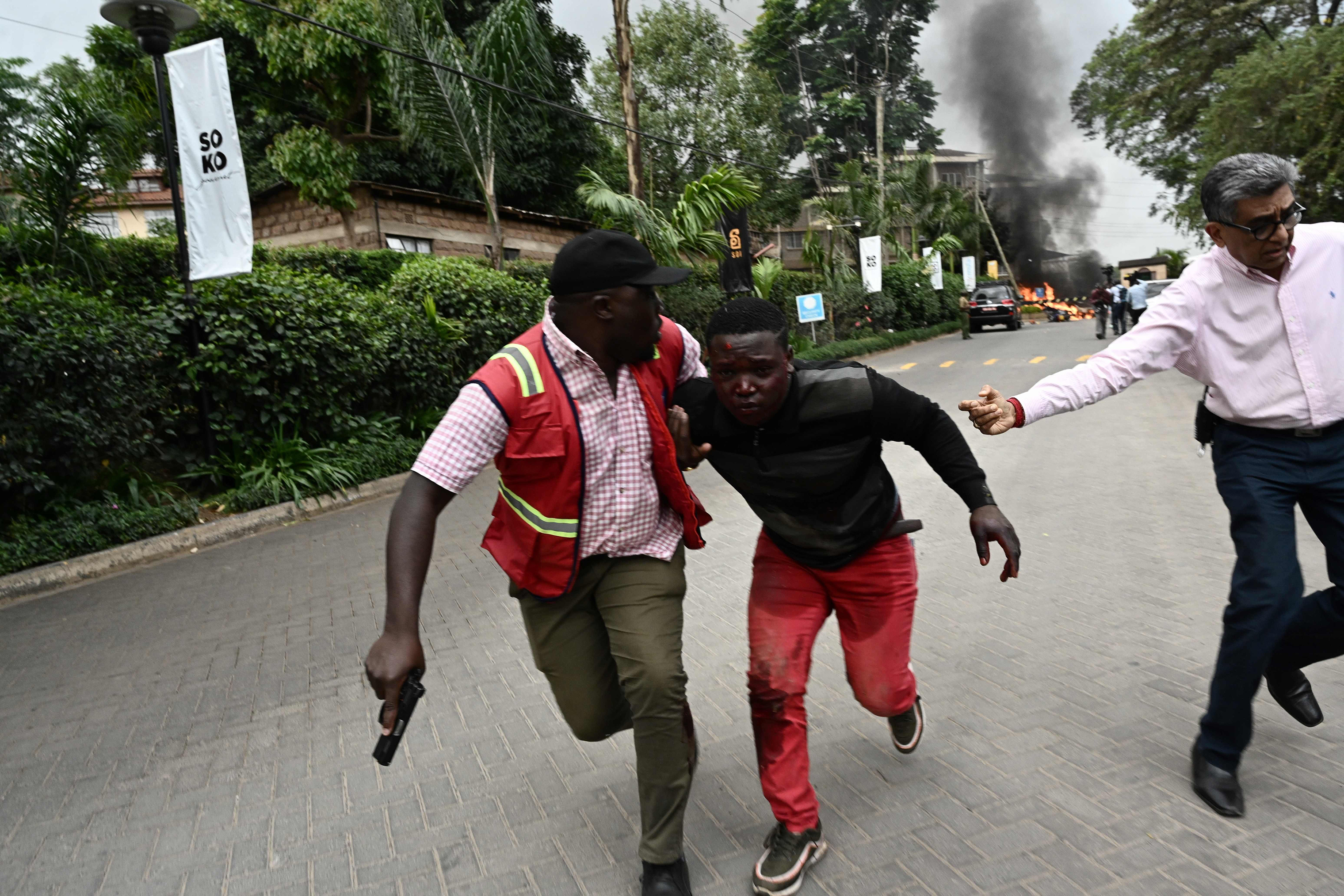 An injured man is evacuated from the scene of an explosion at a hotel complex in Nairobi.