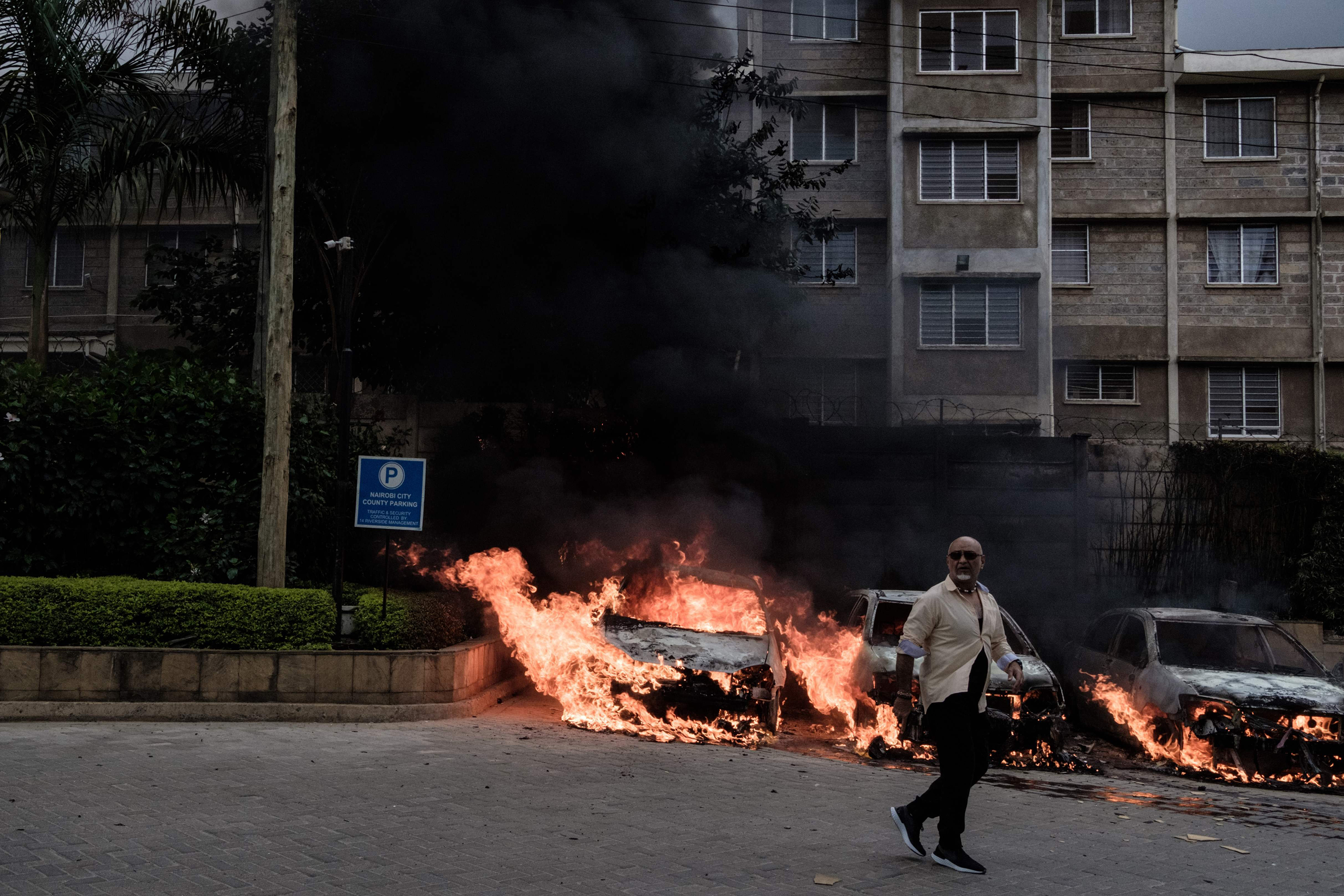 A man passes in front of burning cars that exploded at the entrance of dusitD2 hotel in Nairobi.