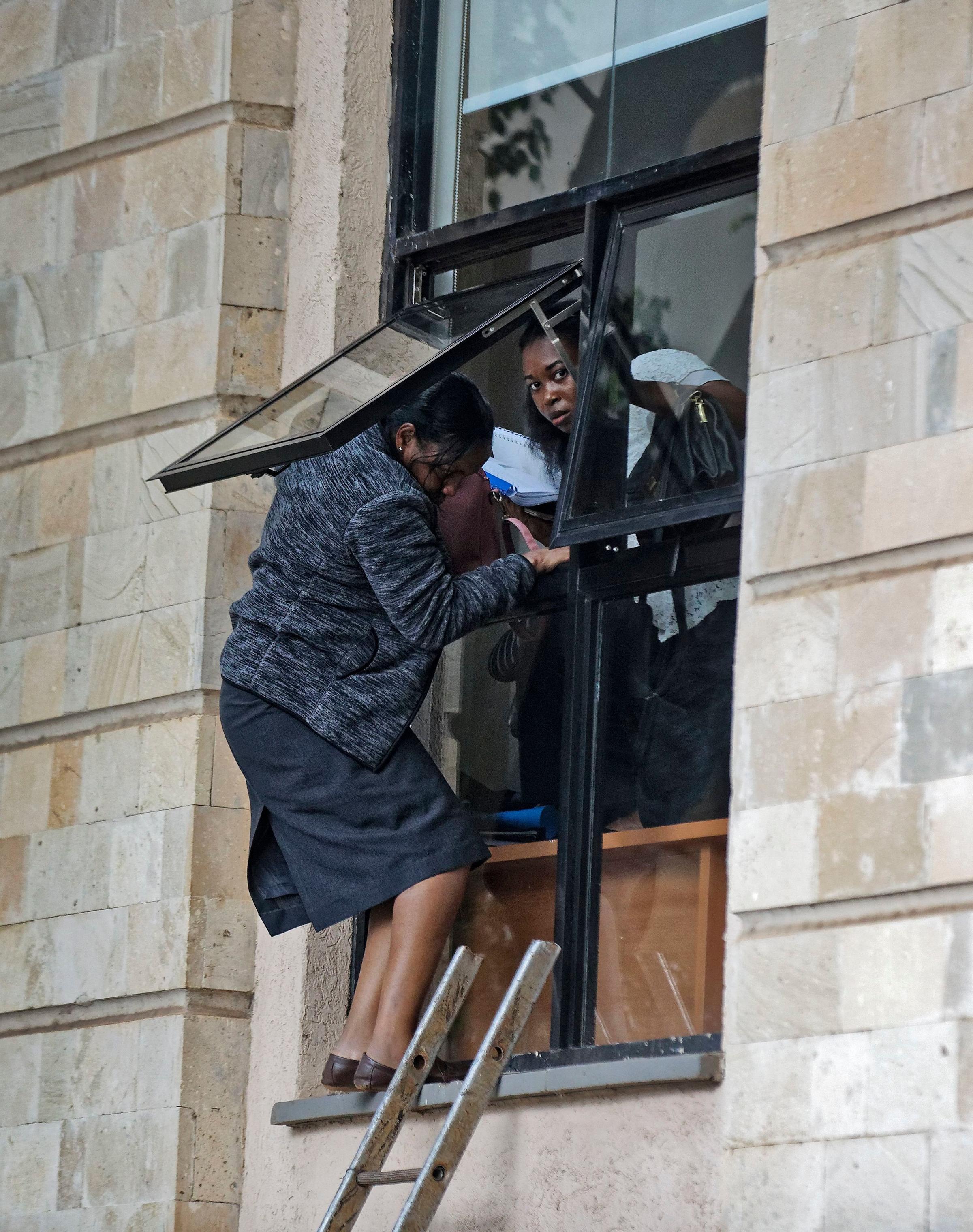 Civilians flee through a window at a hotel complex.