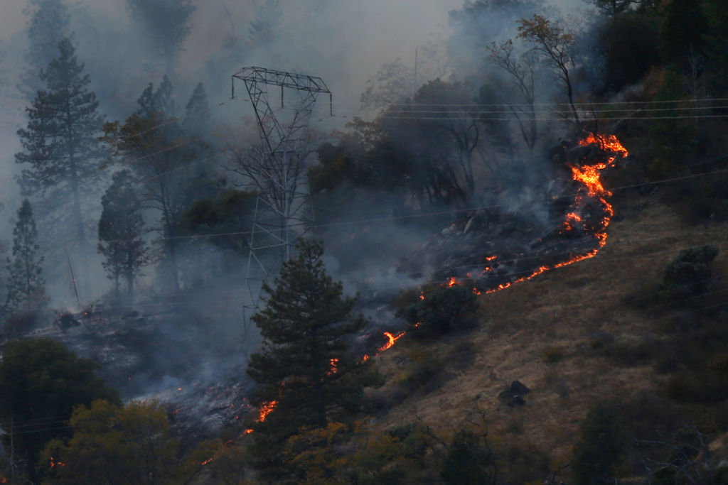 Fire burns around PG&E transmission towers east of Pulga, Calif., on November 12, 2018. The company says it will file for bankruptcy because of the costs of the California wildfires.