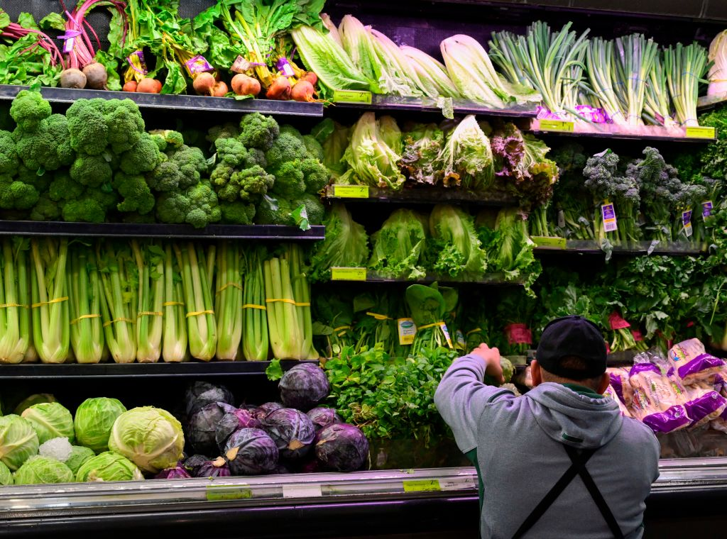 A produce worker stocks shelves near romaine lettuce (top shelf center) at a supermarket in Washington, DC on November 20, 2018. - US health officials warned consumers not to eat any romaine lettuce and to throw away any they might have in their homes, citing an outbreak of E. coli poisoning. The Centers for Disease Control and Prevention (CDC) issued the warning against all Romaine lettuce just two days before the Thanksgiving holiday, when American families gather and feast together. (Photo by Andrew CABALLERO-REYNOLDS / AFP)        (Photo credit should read ANDREW CABALLERO-REYNOLDS/AFP/Getty Images)