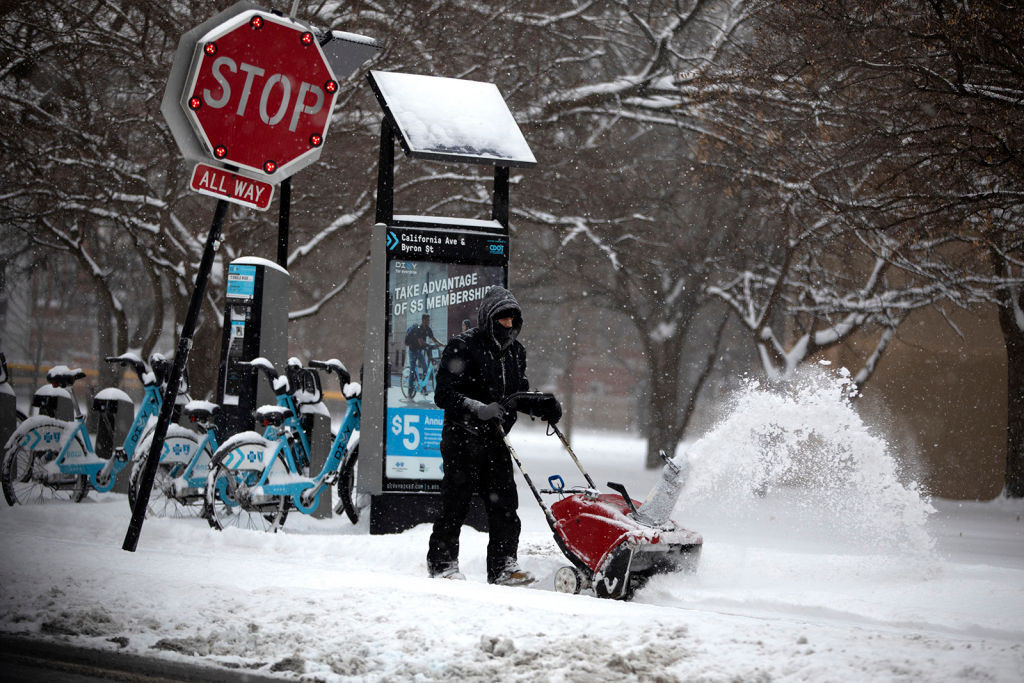 Snow is removed from the sidewalk in front of the McFetridge Sports Center in Chicago on Jan. 19, 2019.