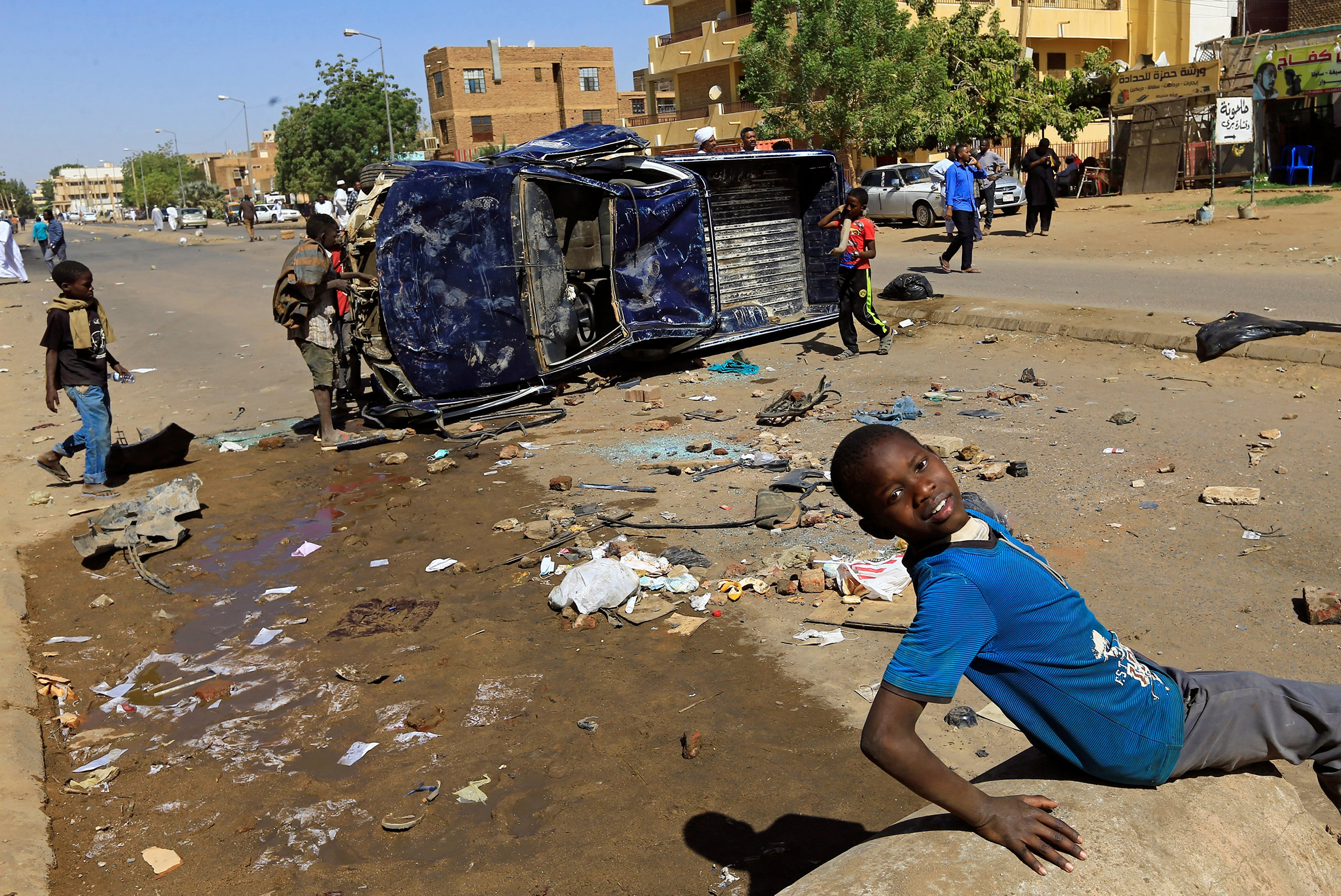 Children play near a police car flipped over and damaged by mourners near the home of a demonstrator who died of a gunshot wound sustained during anti-government protests in Khartoum, Sudan January 18, 2019.