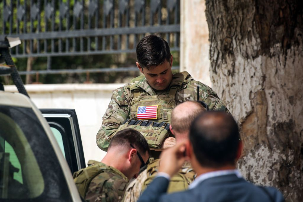 U.S. soldiers stand at attention during a visit of a U.S. delegation to the YPG-held northern Syrian city of Manbij, where the US has a military presence, on March 22, 2018.