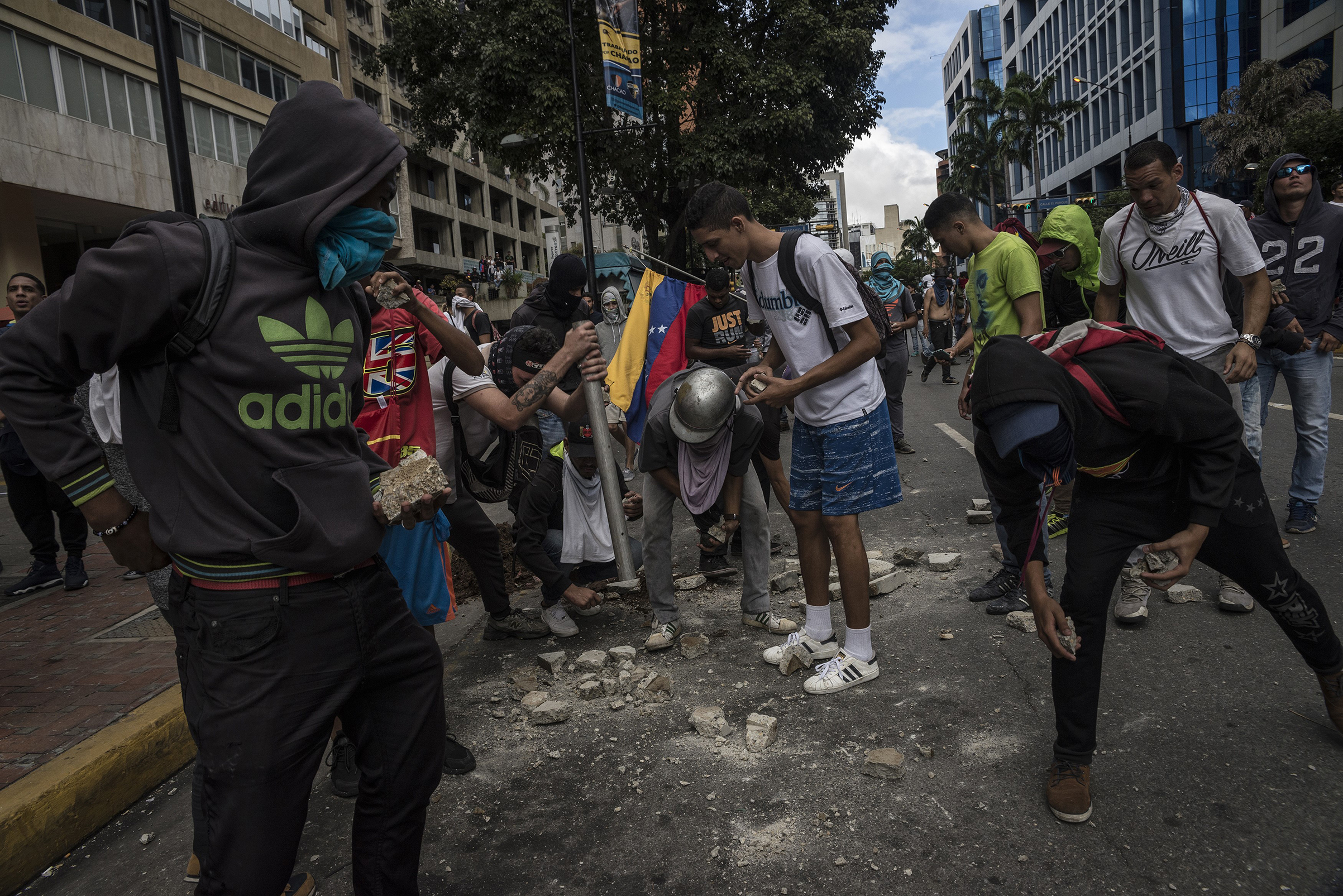 Protesters collect stones to throw against police forces after Juan Guaido, leader of the opposition-controlled congress, declares himself interim president on Jan. 23, 2019.