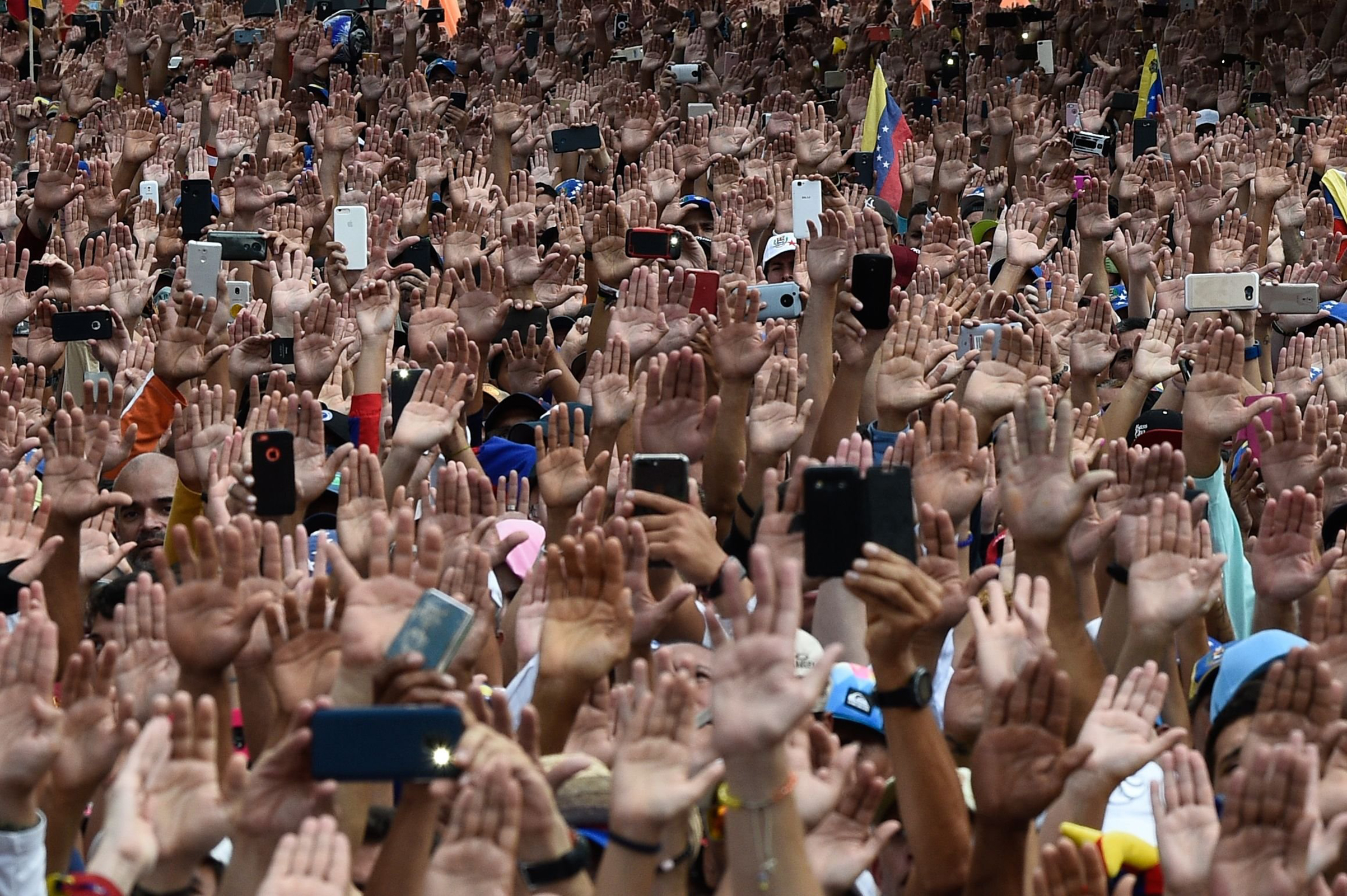 People raise their hands during a massive anti-government rally against Venezuelan President Nicolás Maduro in Caracas on Jan. 23, 2019.