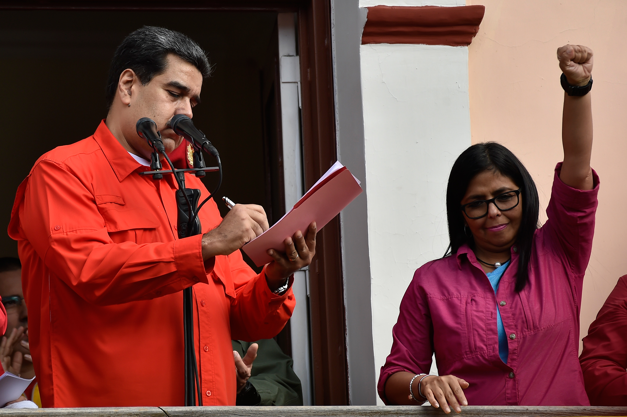 Venezuela's President Nicolás Maduro, next to Vice President Delcy Rodríguez, signs a document breaking off diplomatic ties with the U.S. at a balcony at the Miraflores Presidential Palace in Caracas on Jan. 23, 2019.