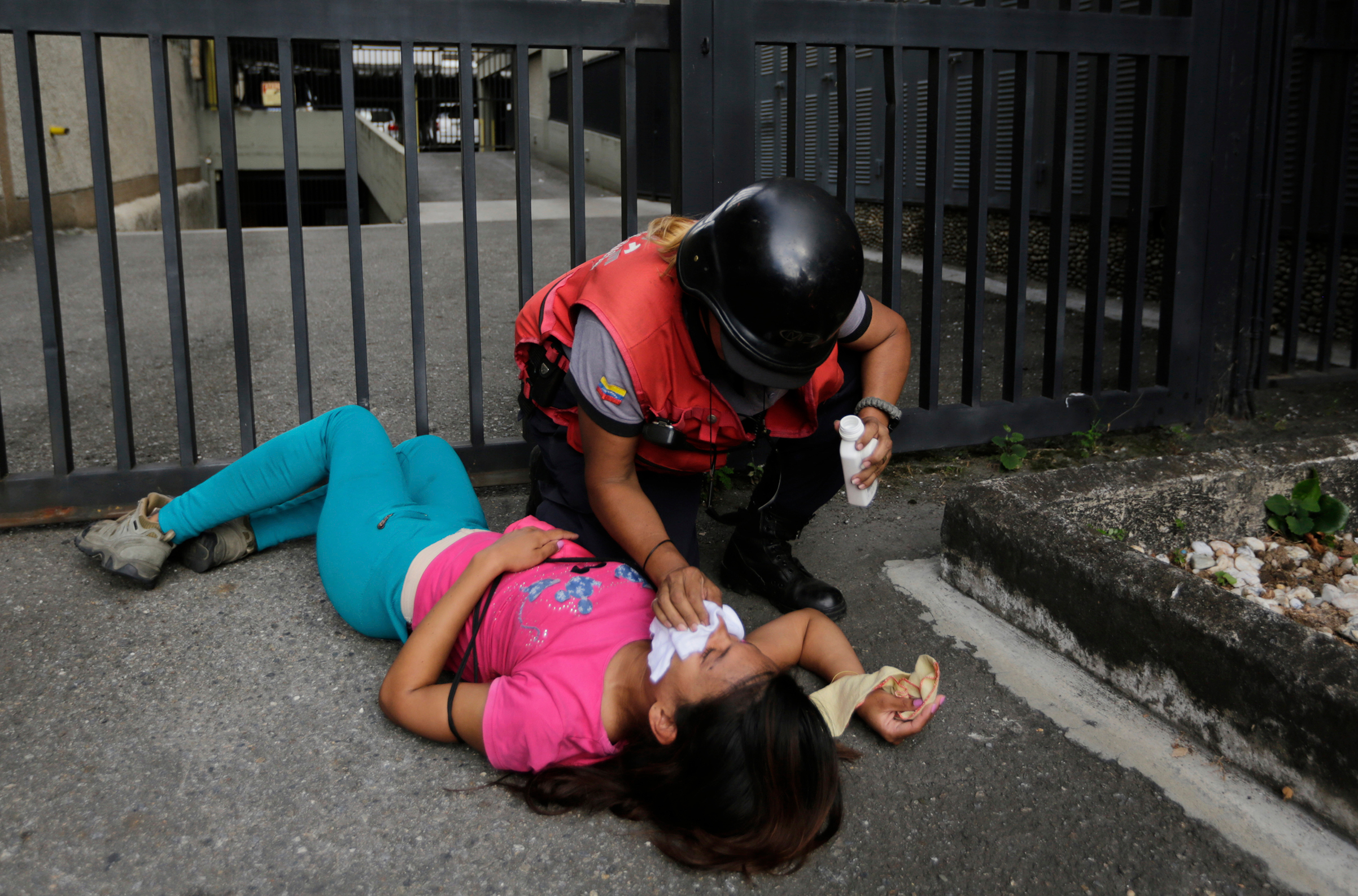 An anti-government protester overcome by tear gas is aided by a paramedic during clashes after a rally demanding the resignation of President Nicolas Maduro in Caracas on Jan. 23, 2019.