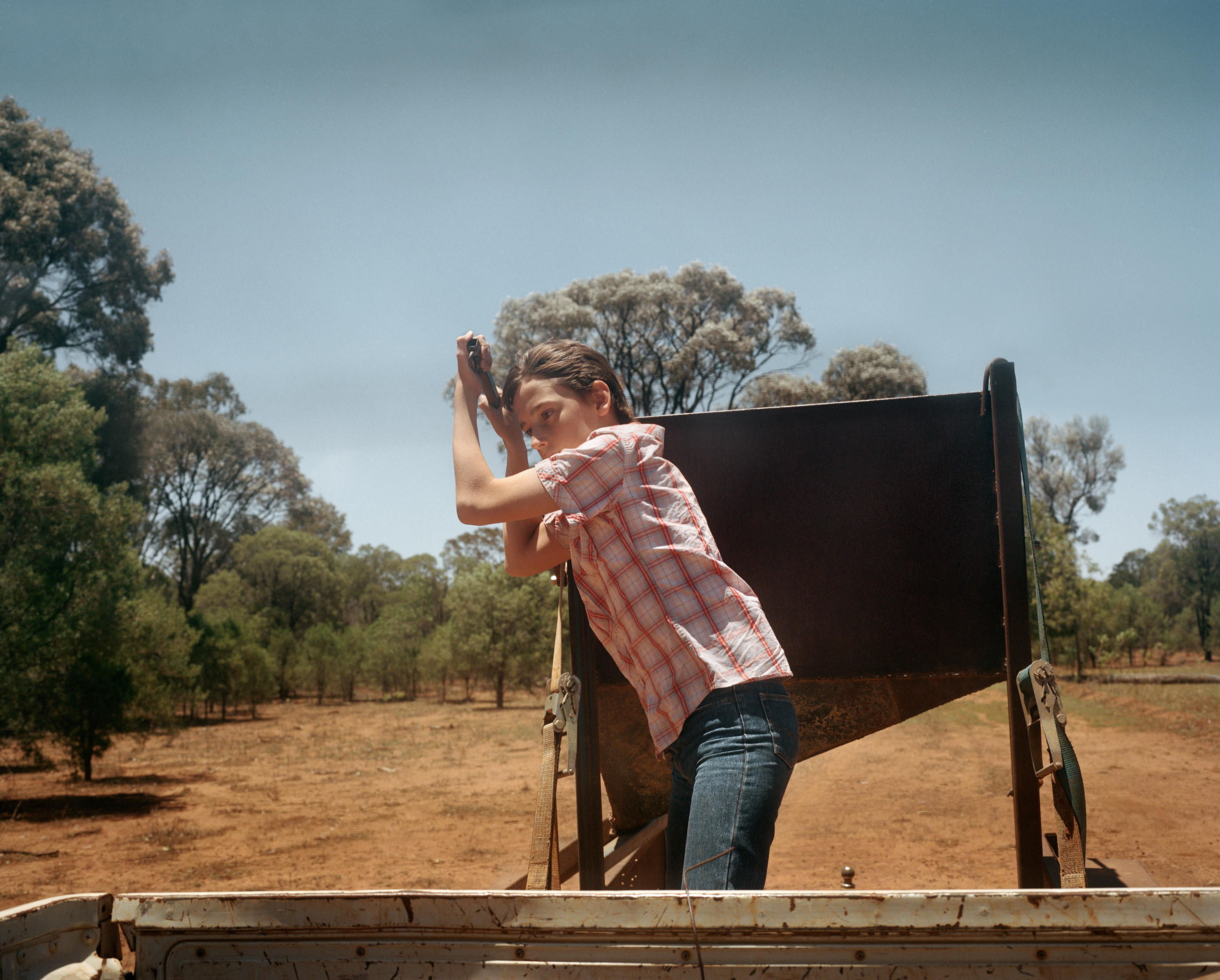 Nicholas Clark, 12, releases feed for sheep on Kandimulla Property in Queensland in November. Without an ability to grow food naturally, Kandimulla owner Kent Morris is forced to buy food to feed his livestock.