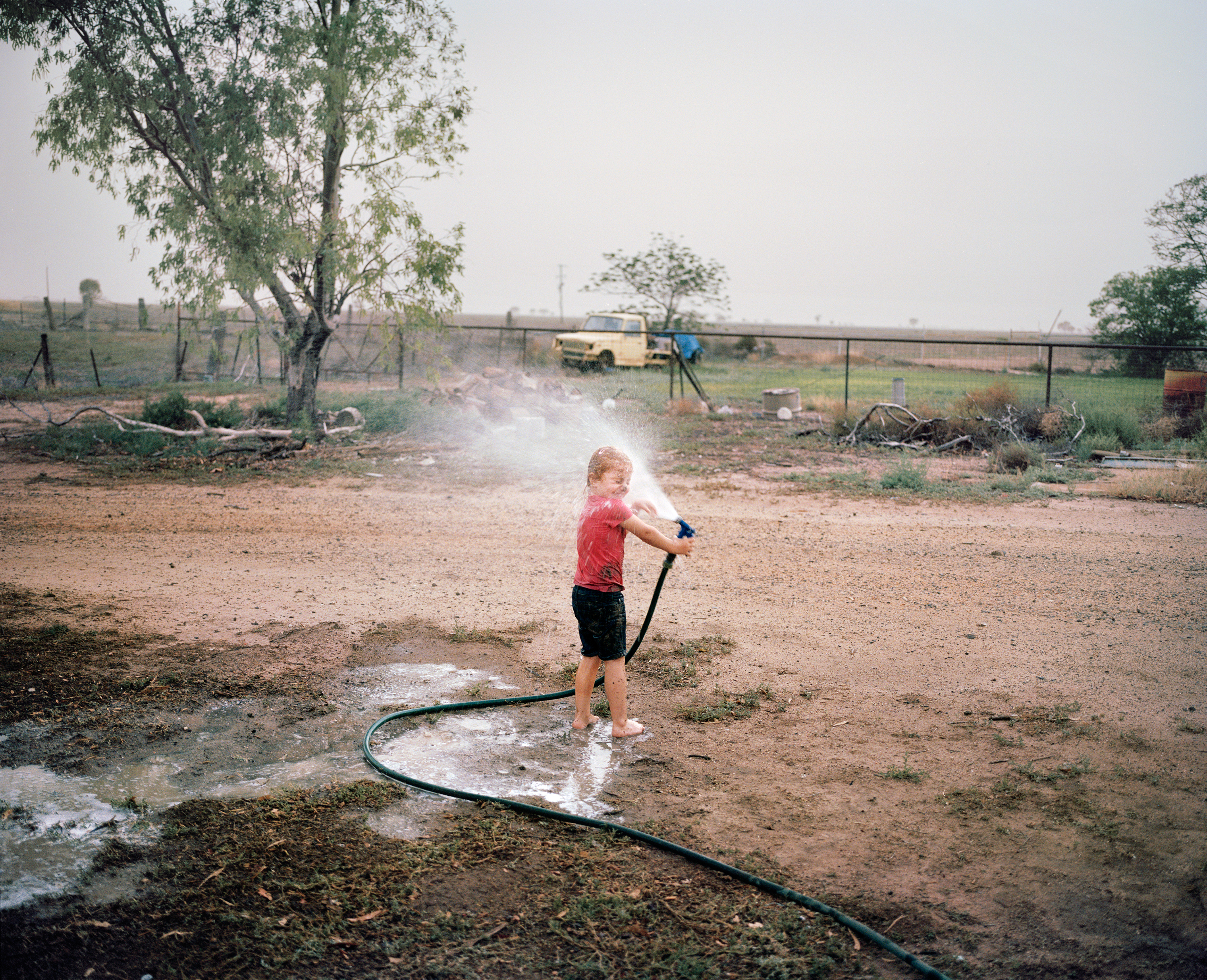 The daughter of farmer Ben Hawk plays with a hose at a Come by Chance store in New South Wales in December. Hawk did not plant crops last year because of the drought. While believing it's up to farmers to run a diverse business that is resilient enough to drought, Hawk says  it will be time to make some tough decisions if it doesn't rain in 2019.
