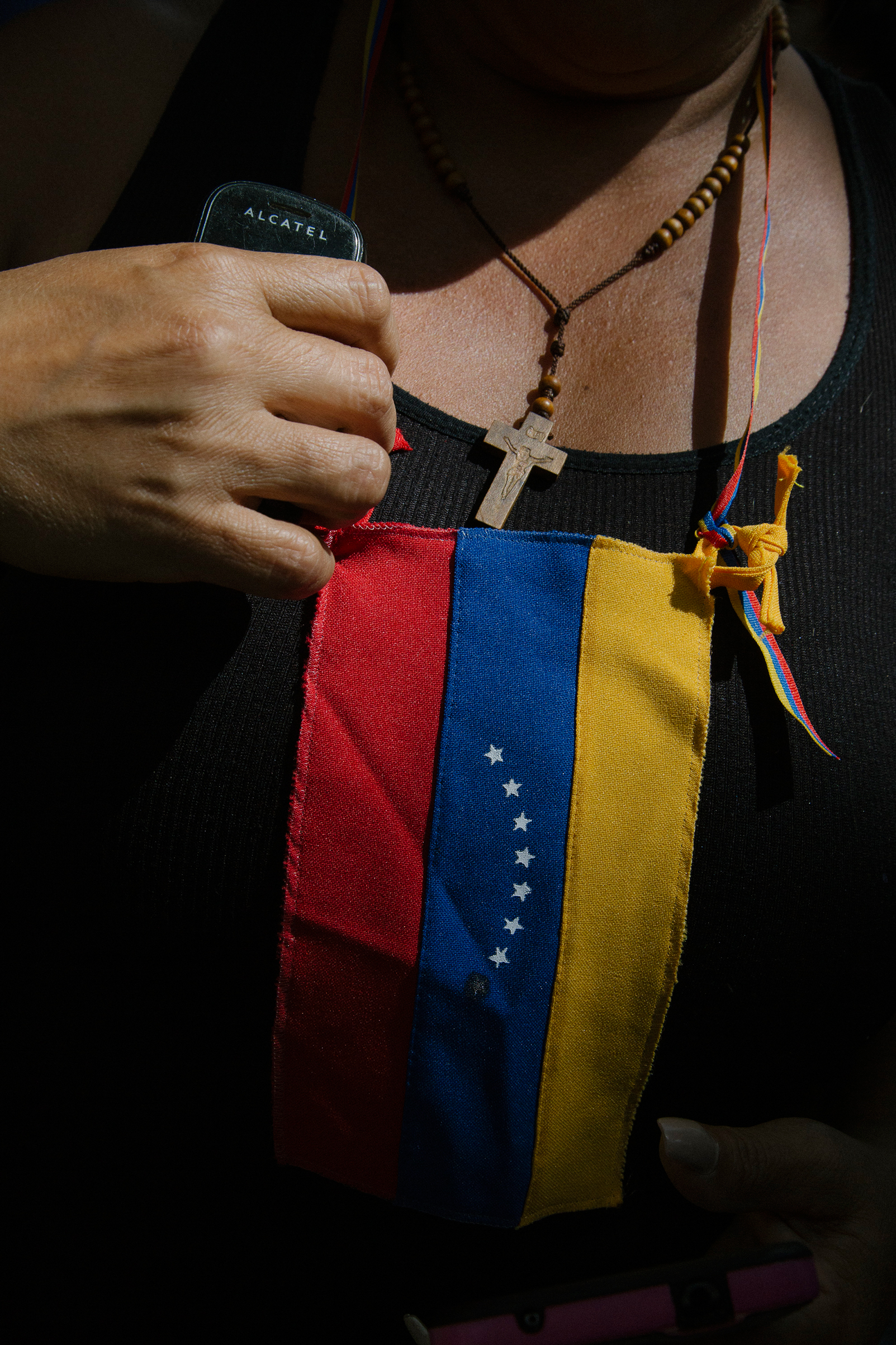 A woman fixes a flag on her chest during a news conference by Guaidó at the Bolivar Square of Chacao in Caracas on Jan. 25, 2019.